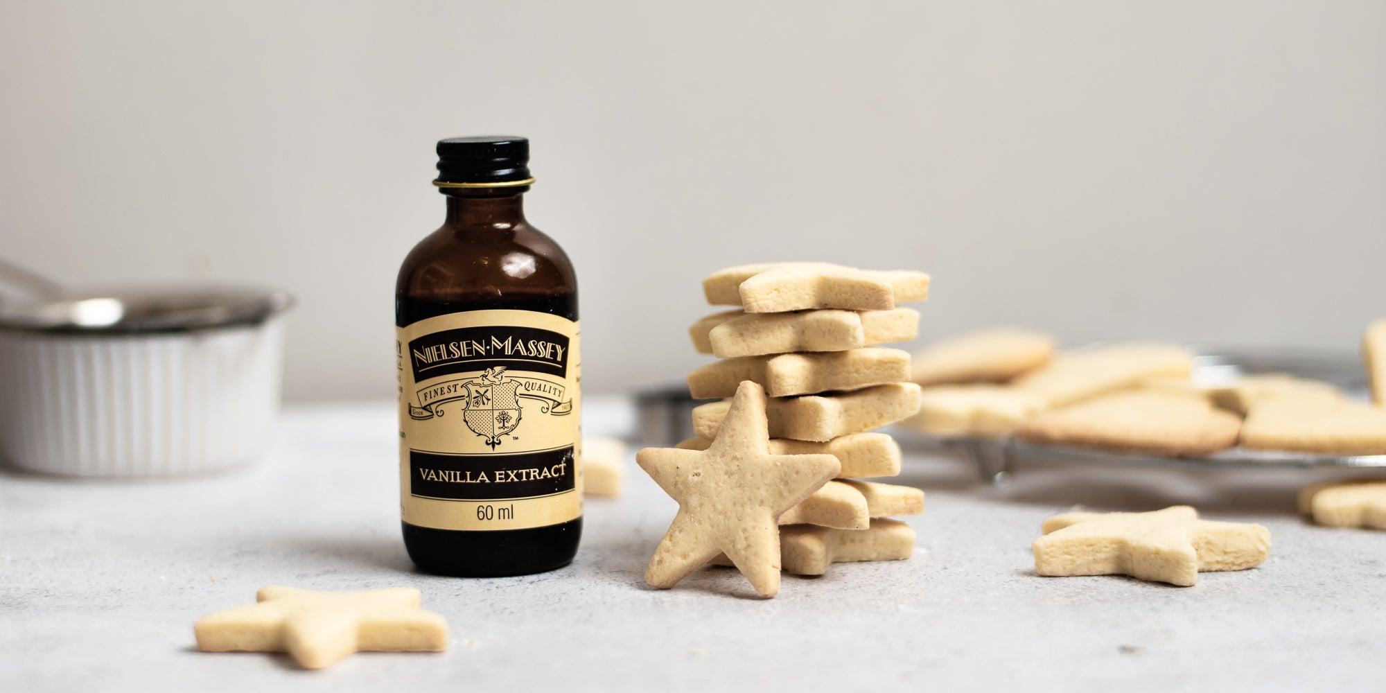 A stack of star shaped gluten free biscuits next to a bottle of Neilsen Massey vanilla extract