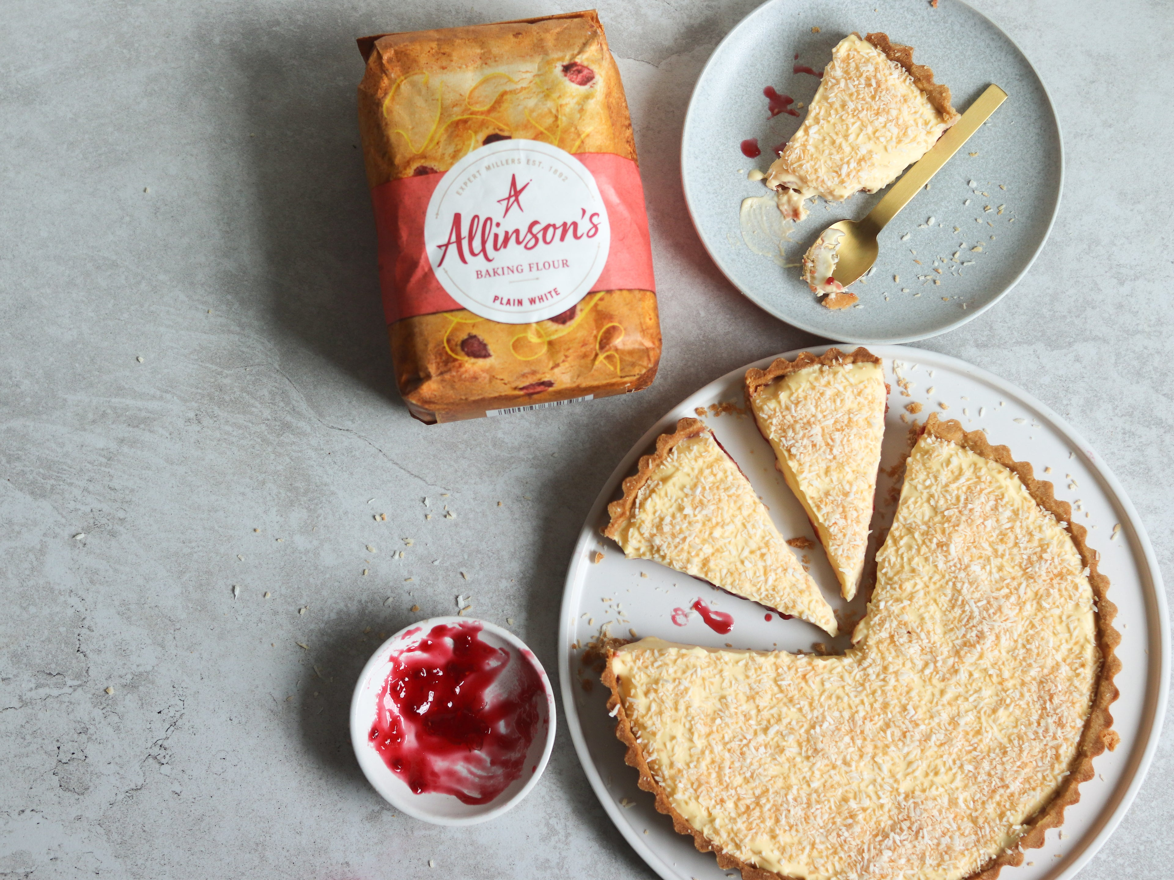 Top view of a Manchester Tart sliced with pieces to serve. Next to a bag of Allinson's Plain Flour and a slice of Manchester Tart on a plate with a spoon covered in toasted coconut
