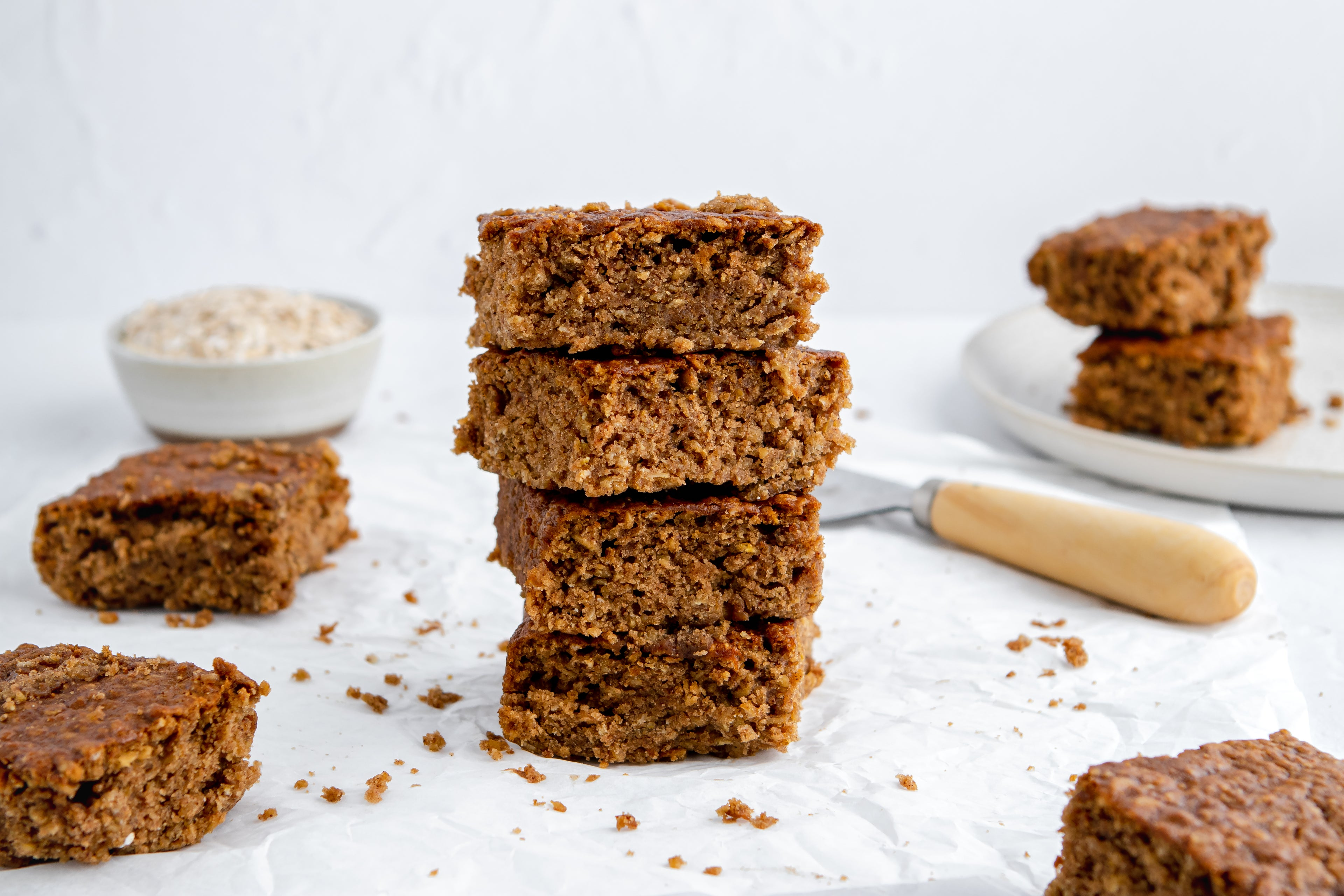 Squares of Sticky Yorkshire Parkin stacked on top of each other, surrounded by crumbs with a bowl of oats in the background