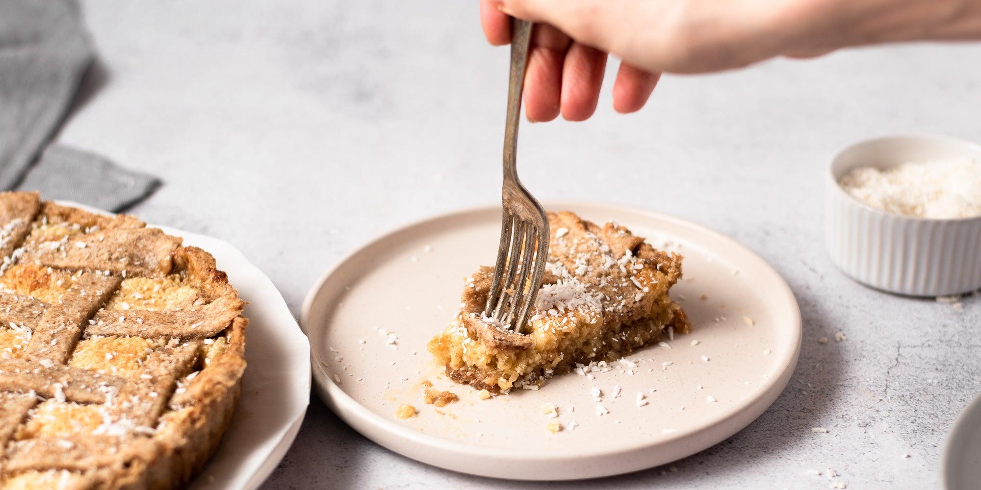 fork in a slice of coconut tart