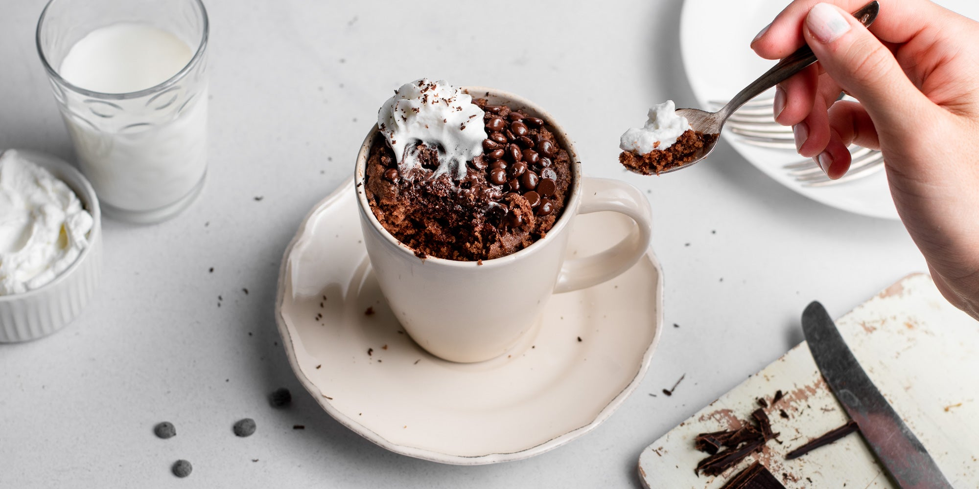 Top view of Chocolate & Peanut Butter Mug Cake with a hand dipping a spoon into the mug cake. Next to a glass of milk, and a ramekin of whipped cream