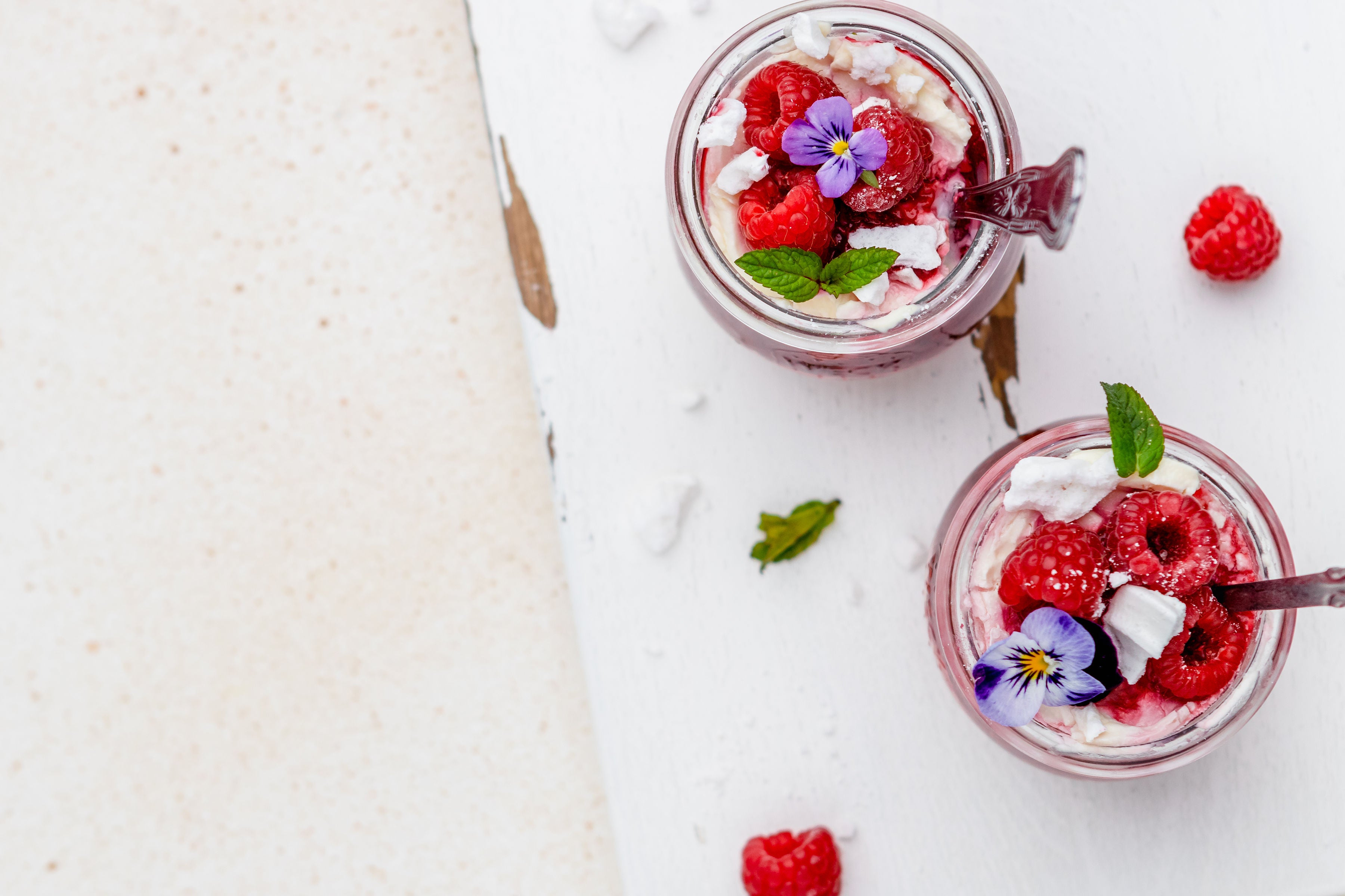 Overhead shot of two eton mess topped with raspberries and flowers