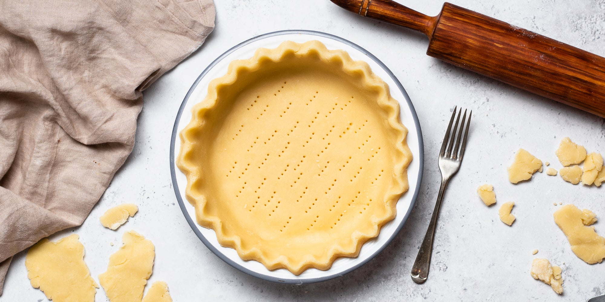 Shortcrust Pastry in a pastry tin, pricked with a fork, with offcuts of Shortcrust Pastry surrounding