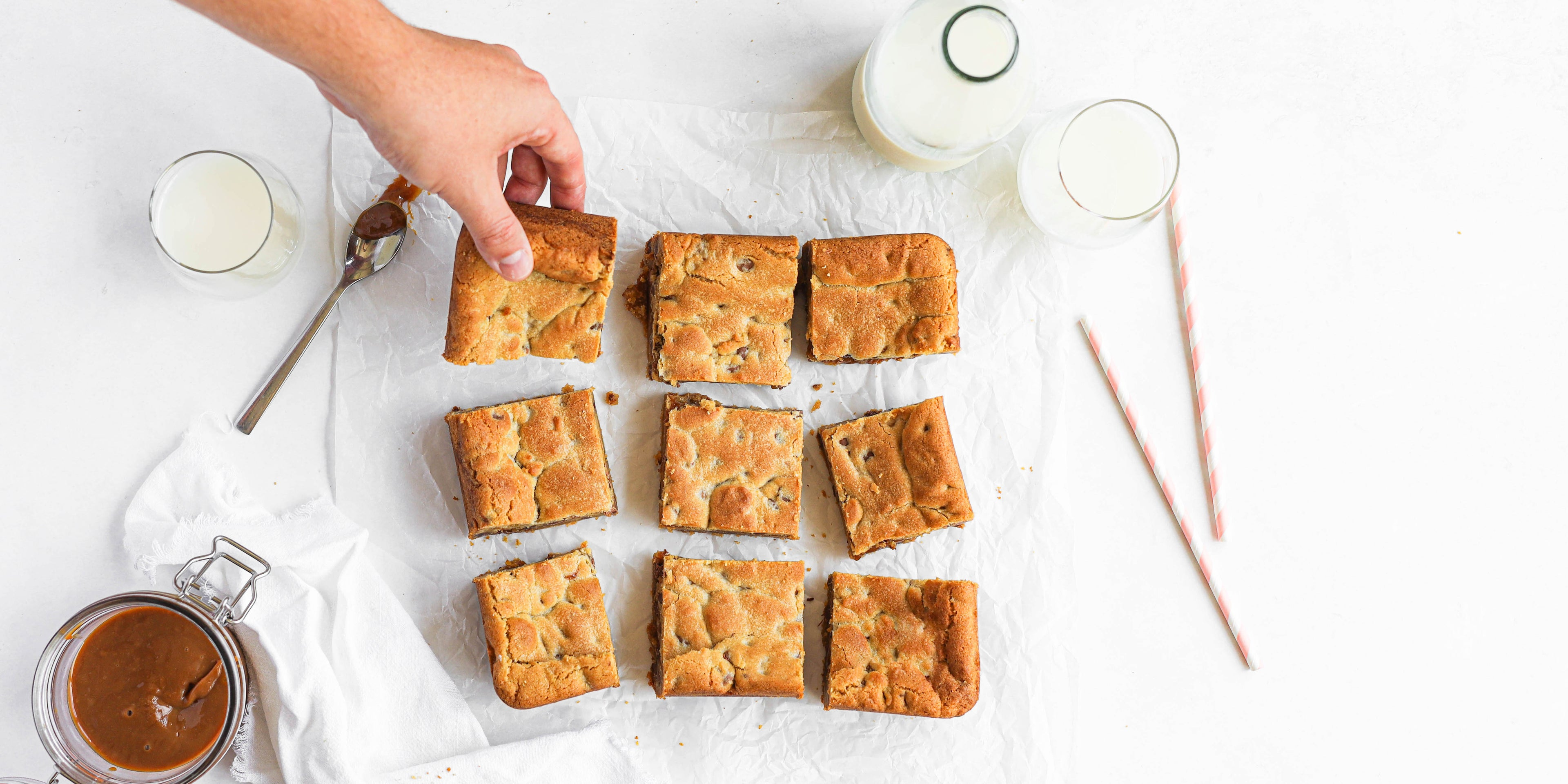 Salted Caramel Cookie Traybake cut onto baking paper, with hand reaching for a square