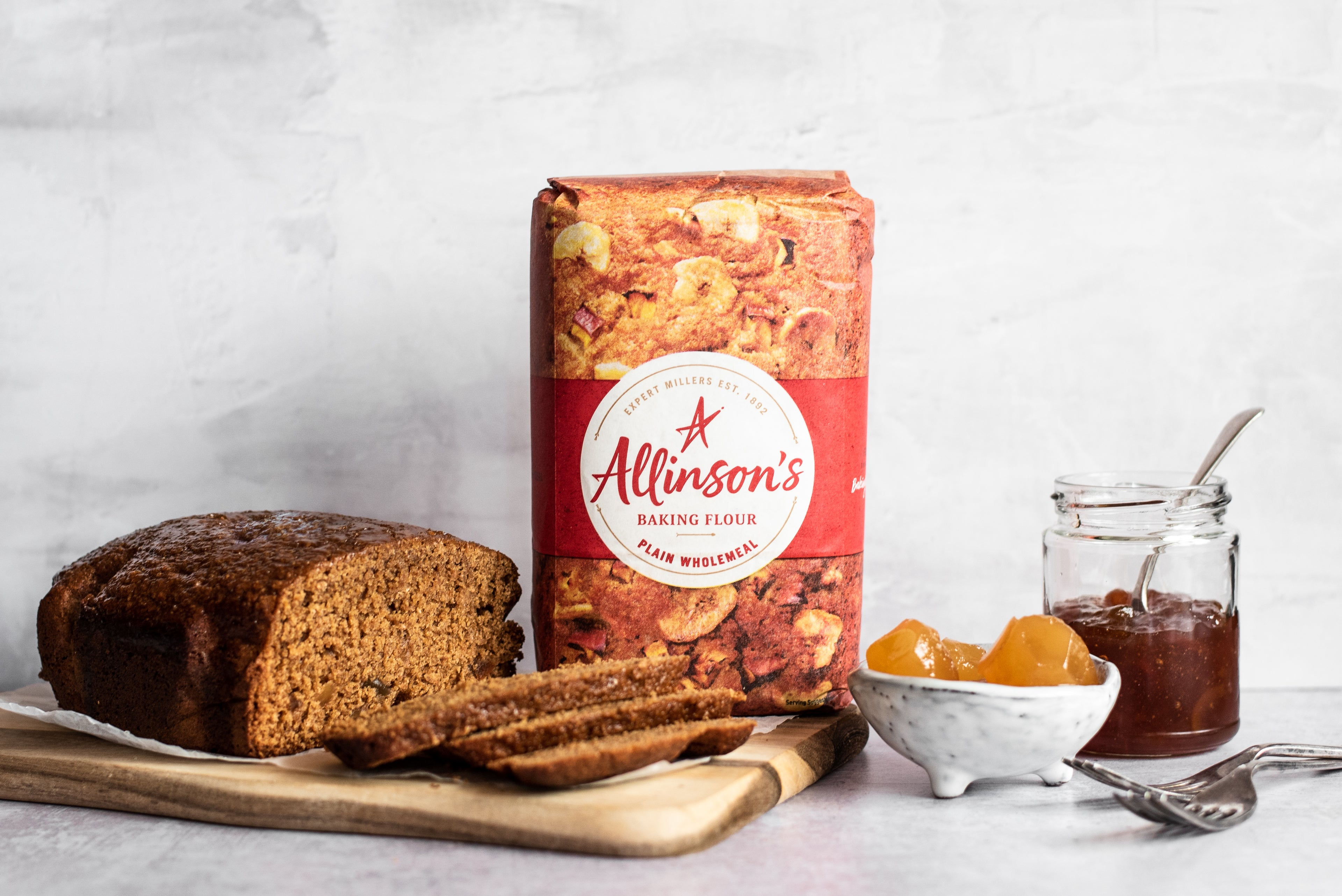 Gingerbread loaf with slices infront, flour pack, bowl of ginger and marmalade in a jar