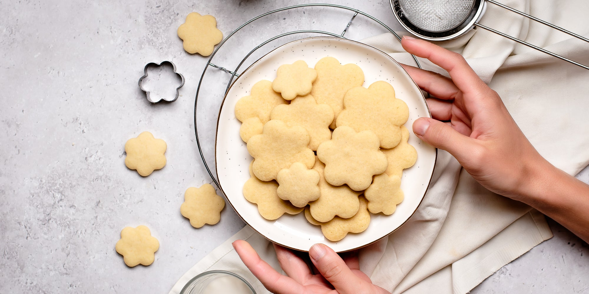 Hands holding a plate of biscuits baked with the Basic Biscuit Dough recipe next to biscuit cutters and a sieve