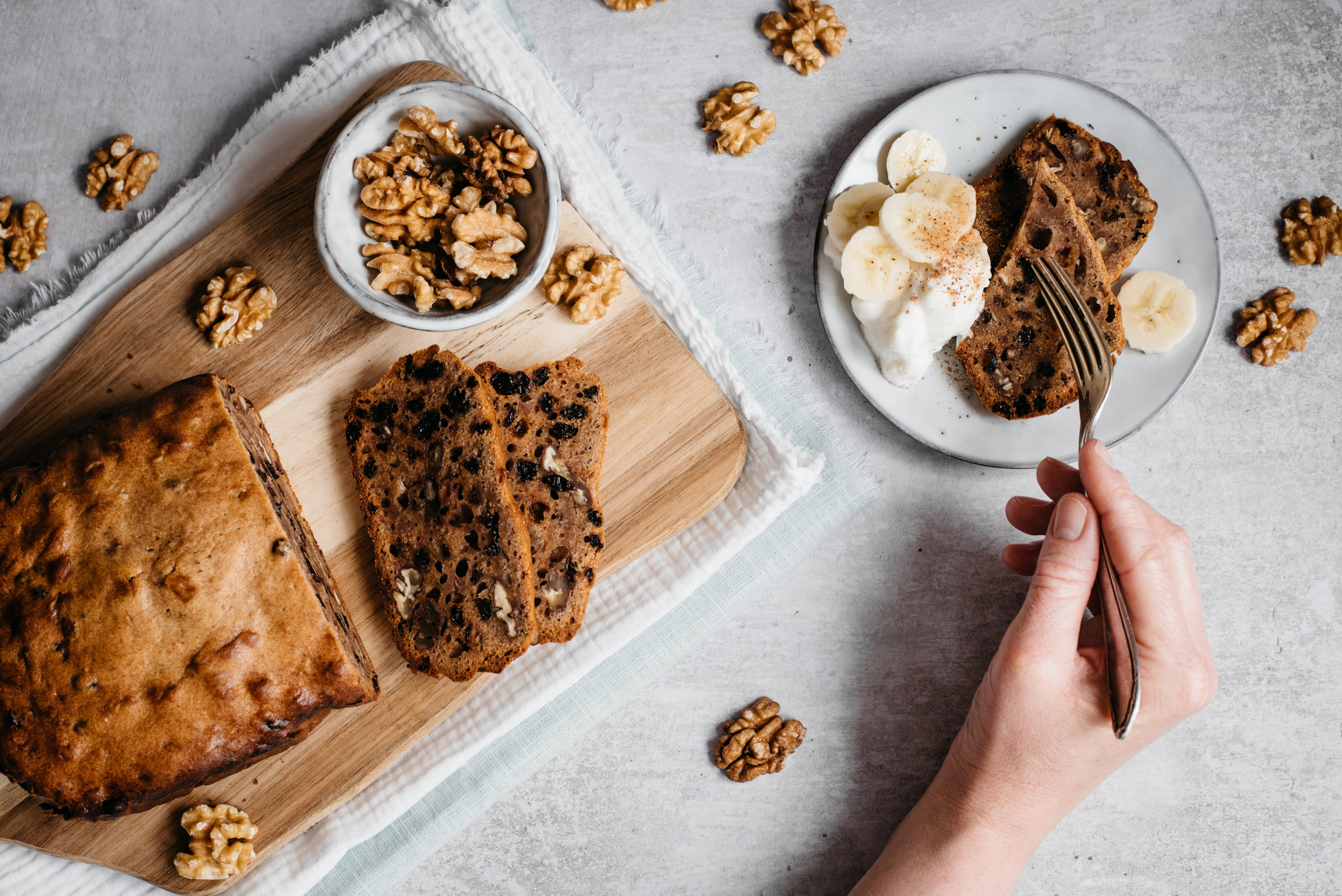Overhead shot of banana bread loaf, slices infront, bowl of walnuts, plate with slices, fork and hand
