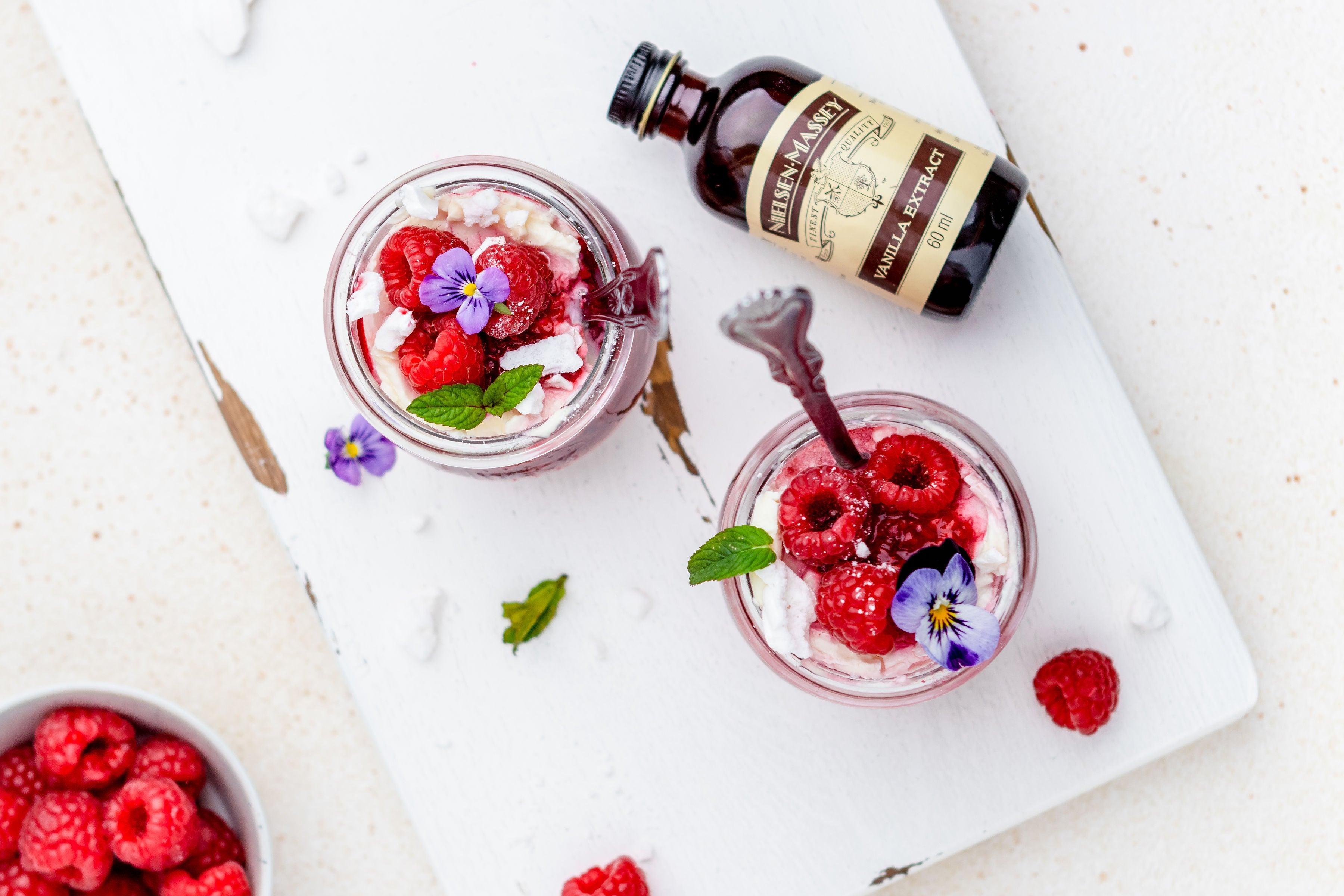 Overhead shot of 2 bowls of eton mess, raspberries, edible flowers and vanilla extract
