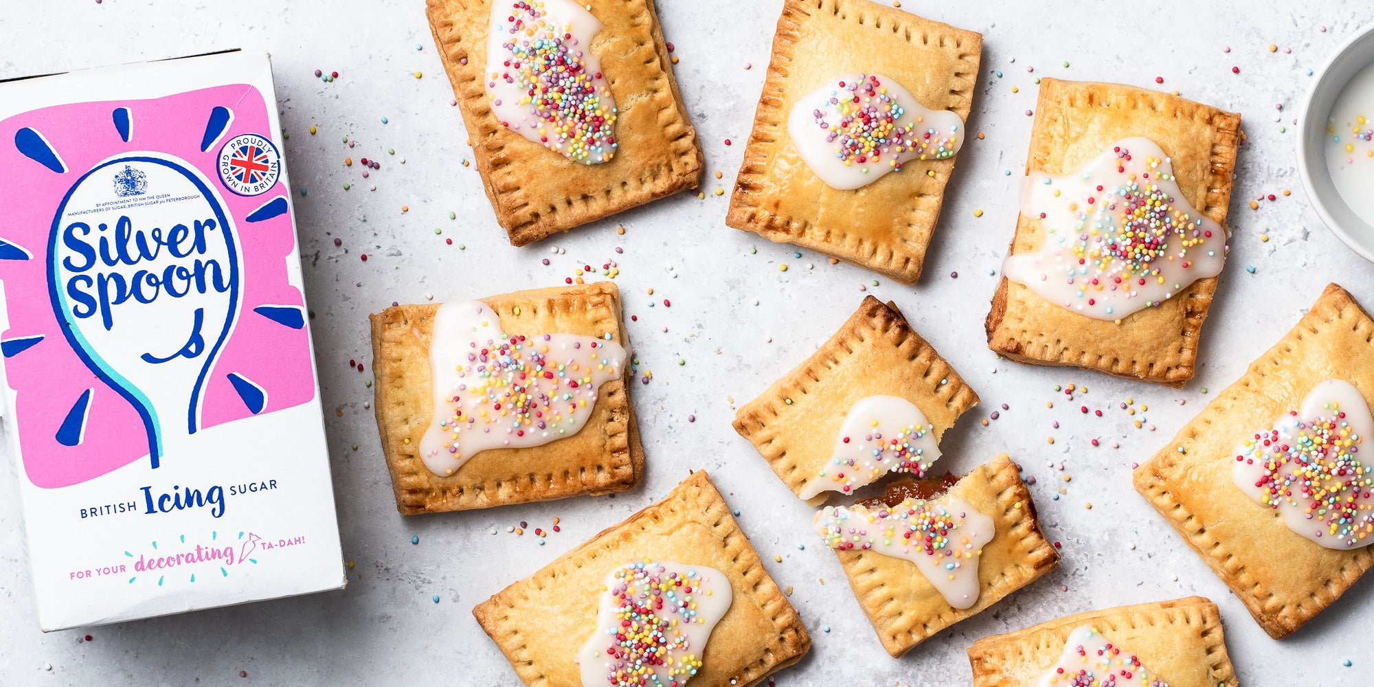 Overhead shot of Pop Tarts with white icing and sprinkles. One broken in half. Icing sugar pack in shot