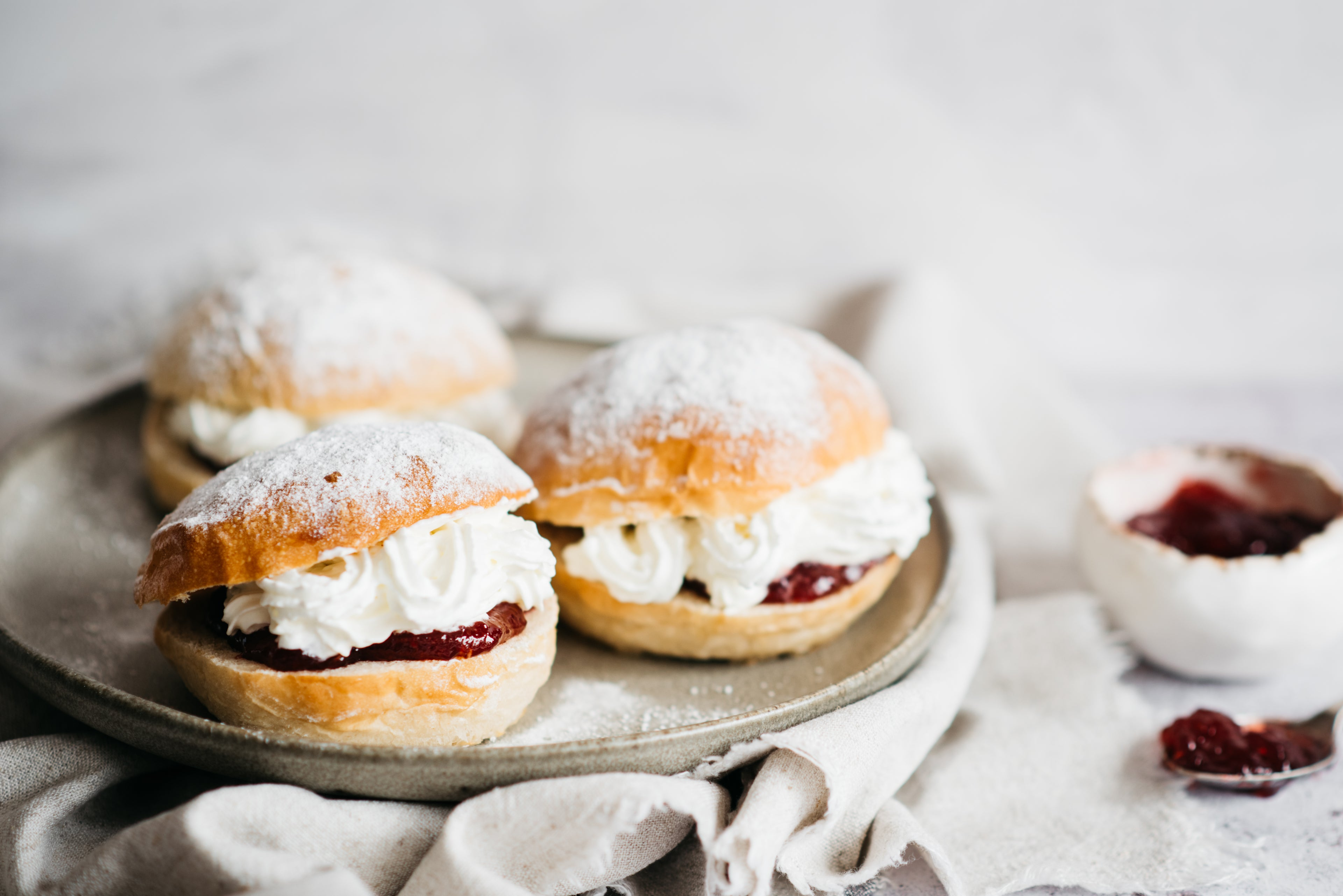 Close up of Devonshire Splits on a plate, filled with cream and jam, with a bowl of jam in the background