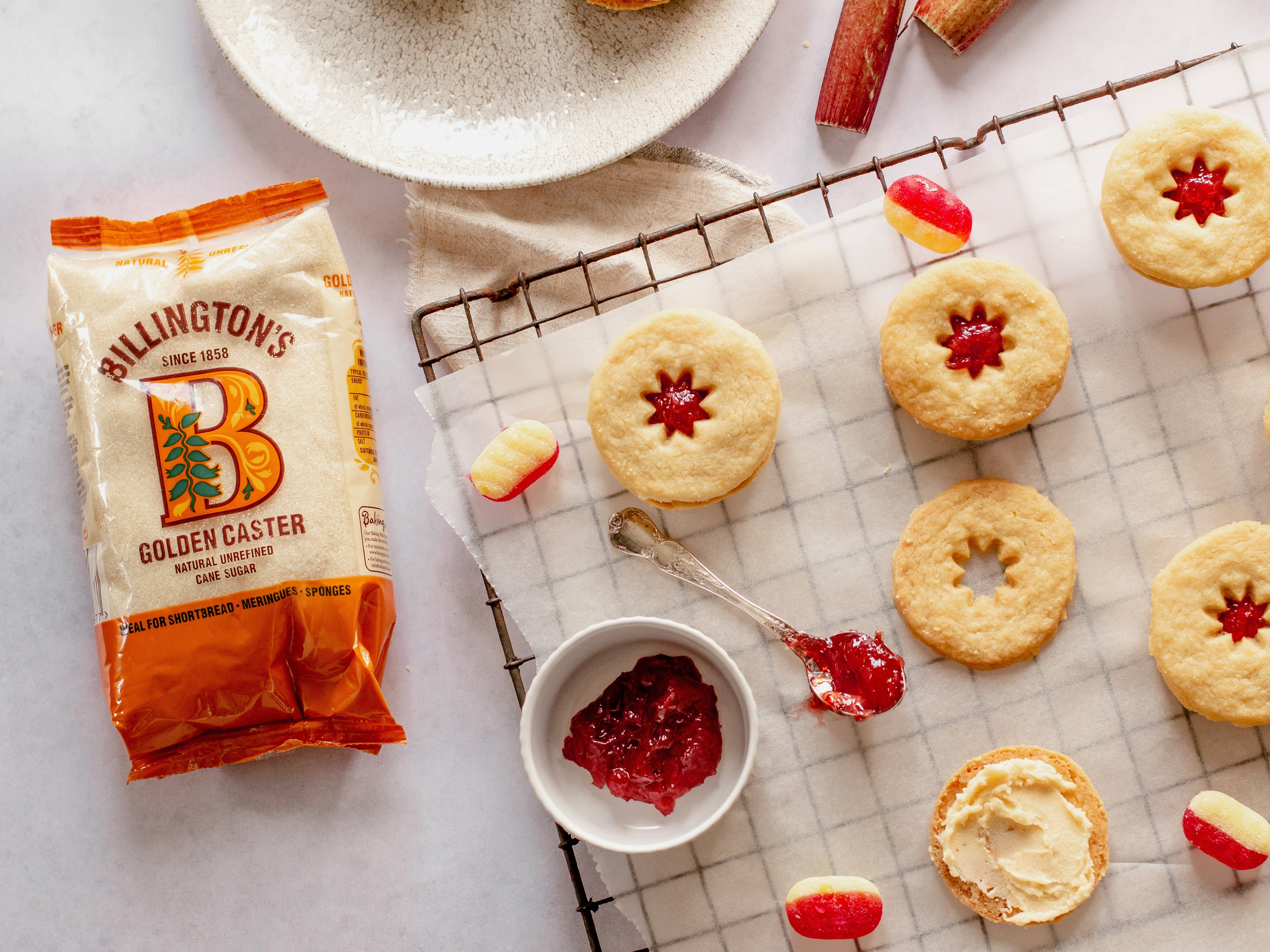 Overhead shot of jammy dodger biscuits being assembled. Sweets, jam in bowl and jammy spoon. Sugar pack in shot