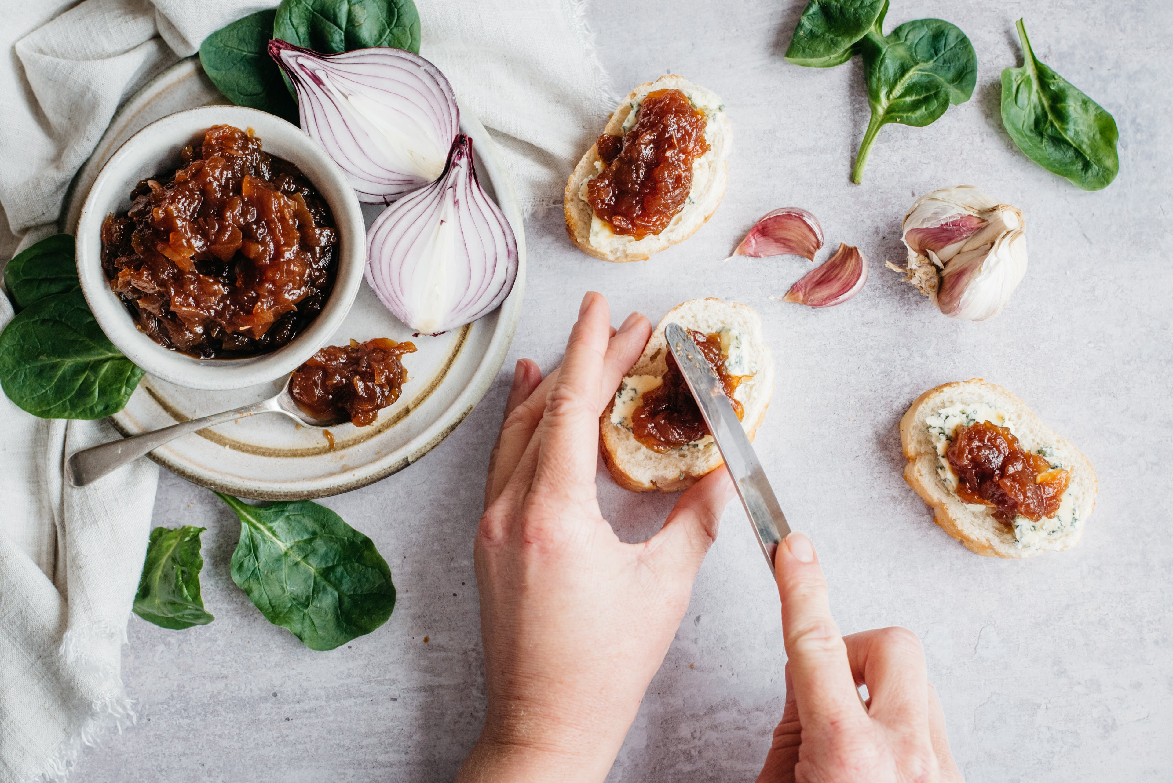 Overhead shot of hands spreading onion chutney on bread, herbs scattered around and pot of onion chutney with spoon