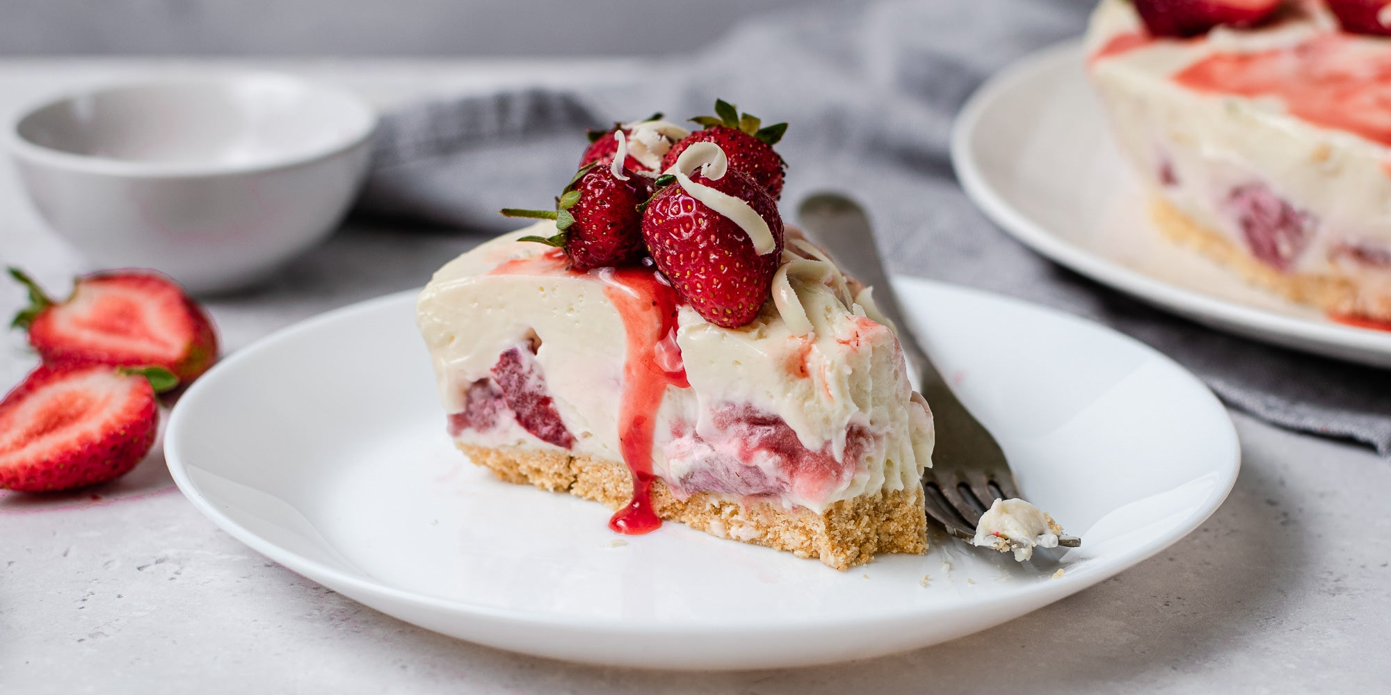 White Chocolate & Strawberry Cheesecake slice, with strawberry sauce running down the cheesecake. Next to a fork on a plate to serve.