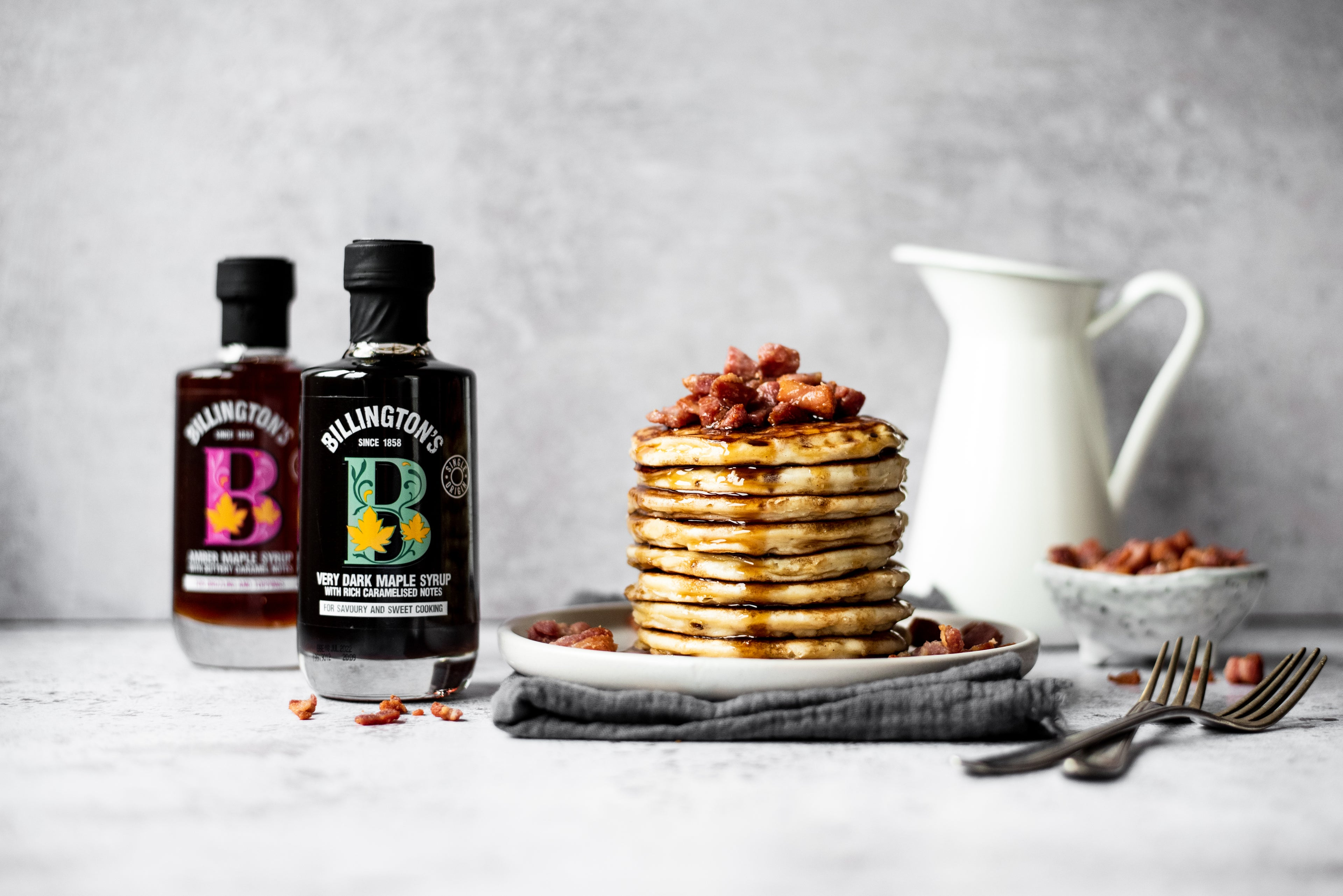 Pancake stack with bacon/ Maple syrup bottles and jug in background