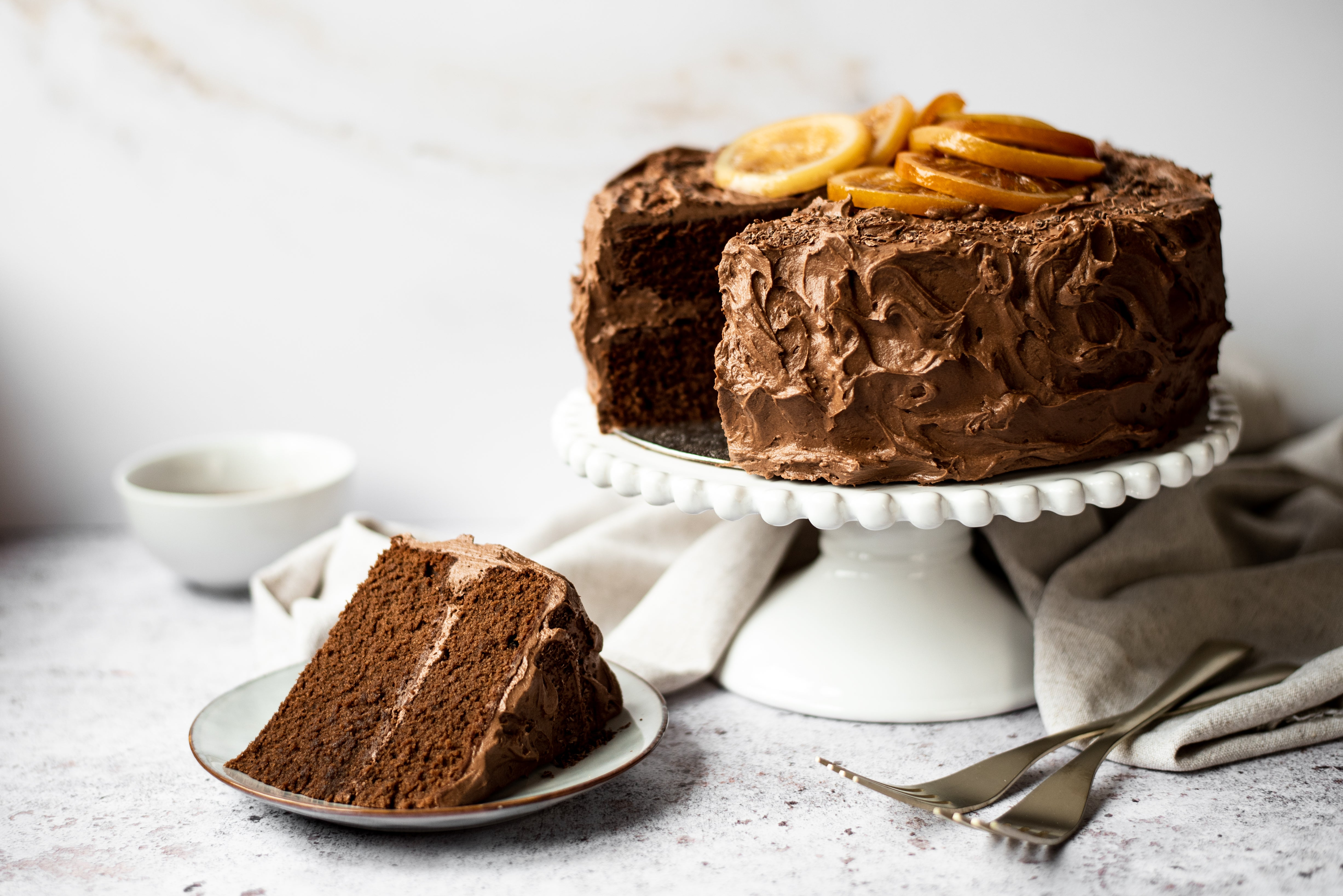 Chocolate cake with orange slices on top with a slice on a plate