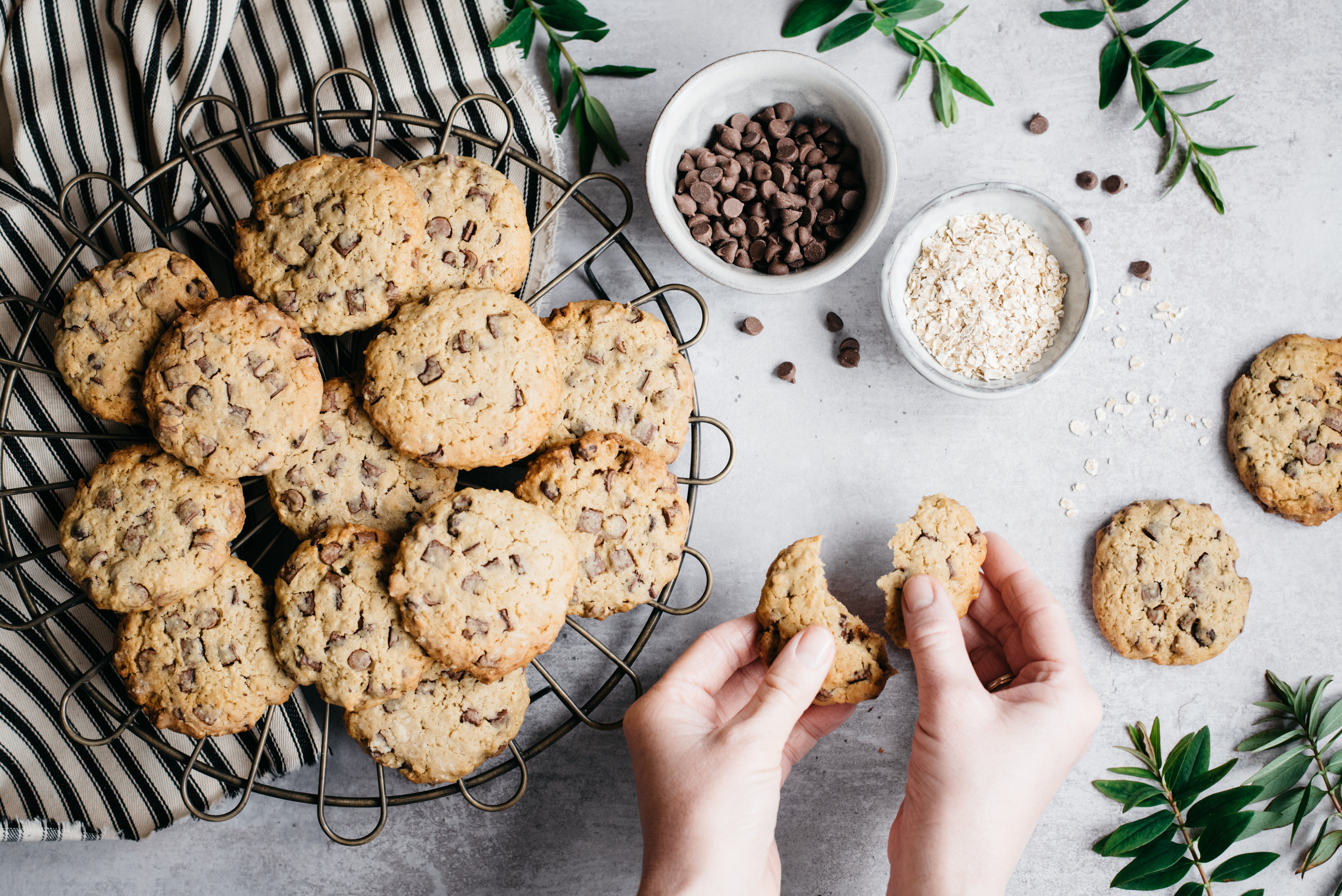 birds-eye view of cookies with hands snapping one in half