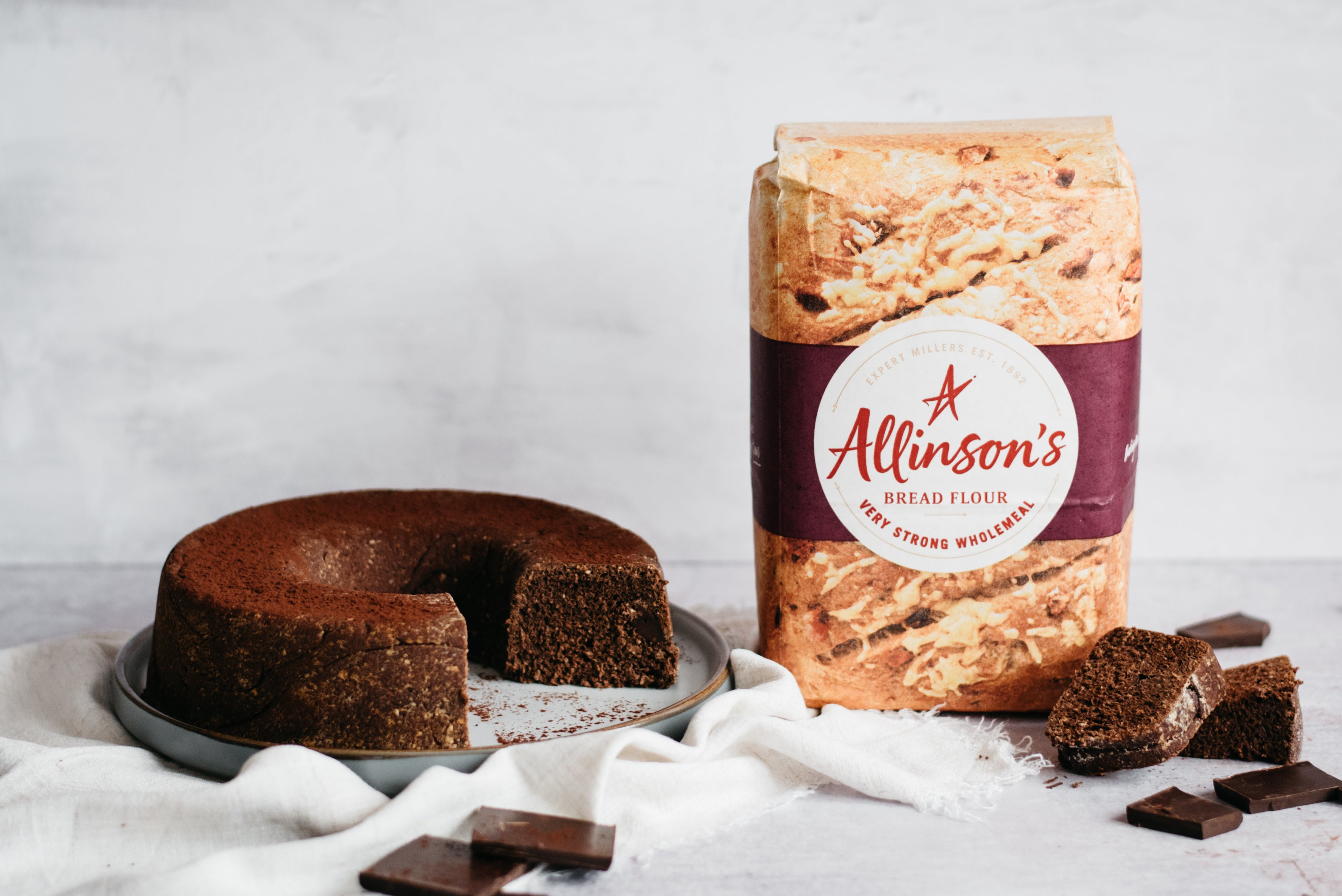 Chocolate Bread next to a bad of Allinson's Very Strong Wholemeal flour next to slices of Chocolate Bread