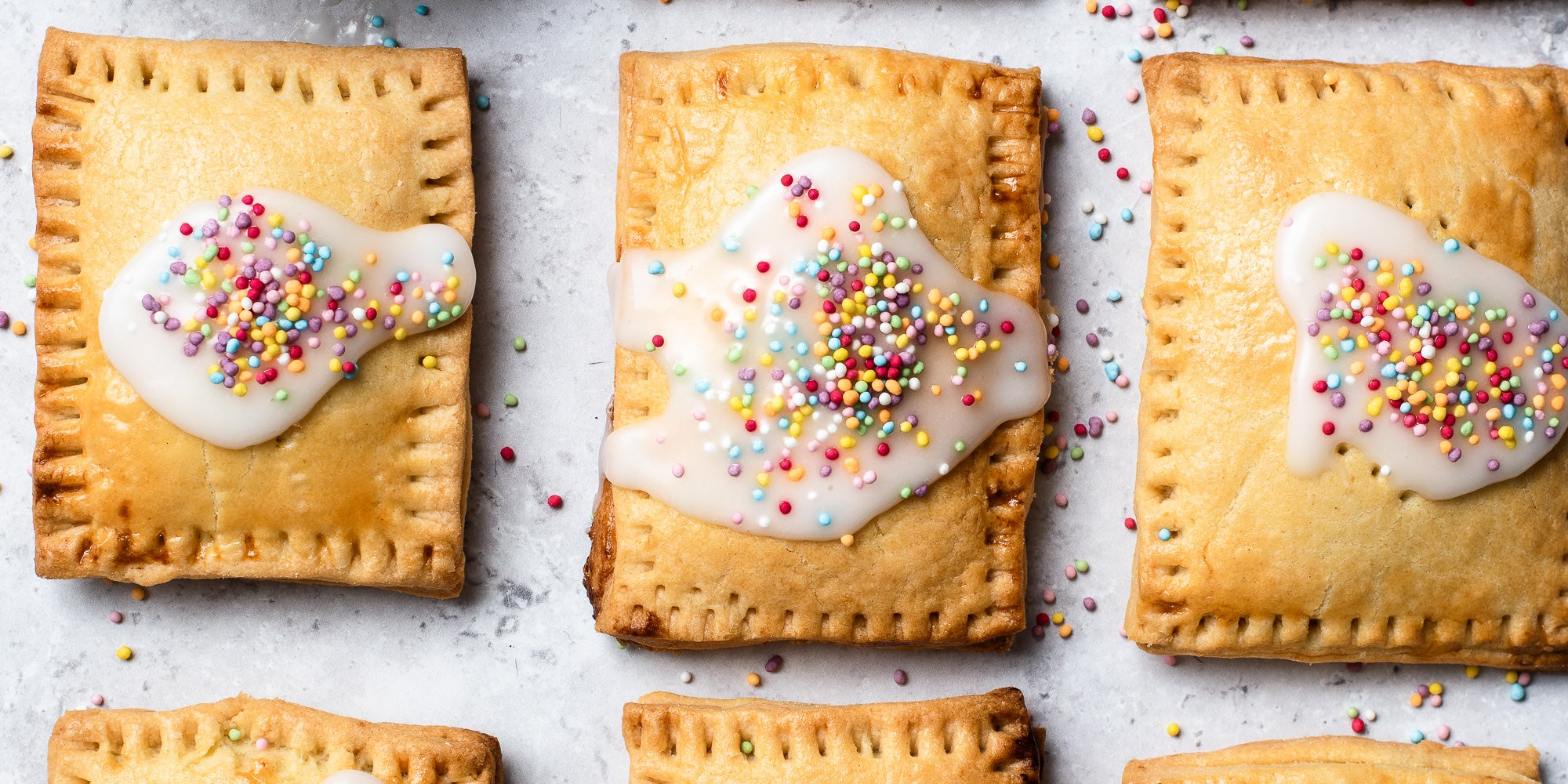 Overhead shot of  3 Pop Tarts with white icing and sprinkles.
