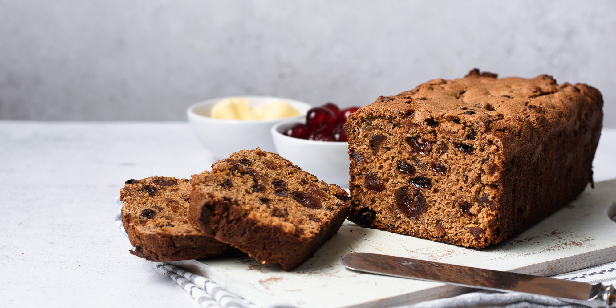 Irish tea loaf with two slices infront and pots of butter and cherries. Knife in shot