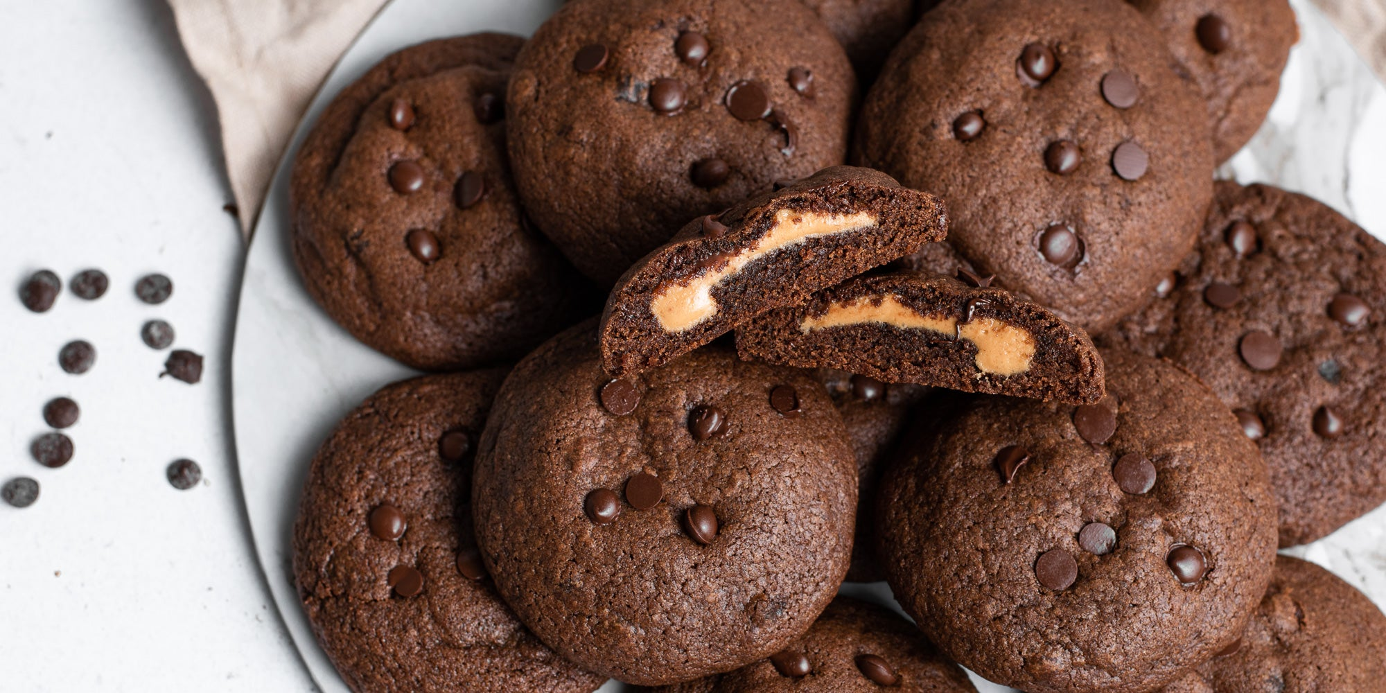Close up Chocolate & Peanut Butter Stuffed Cookies with a cookie sliced in half.