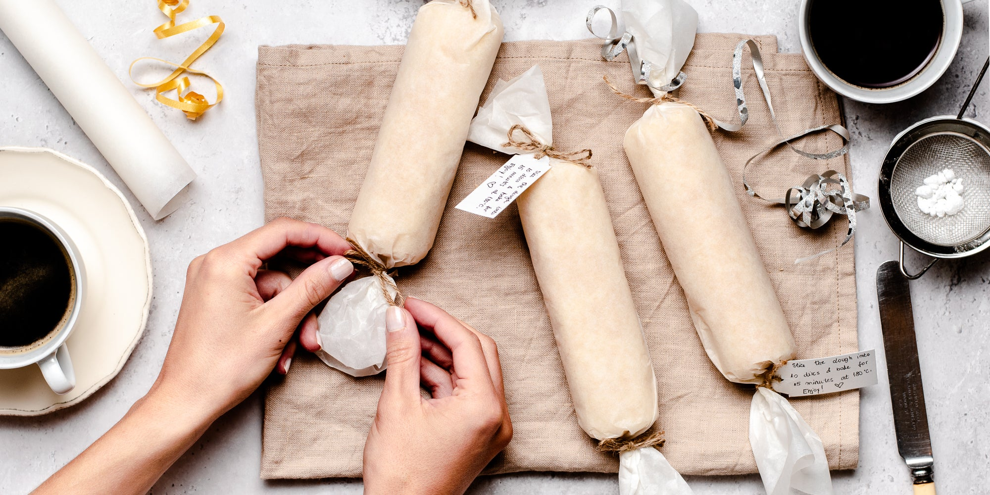 Shortbread Dough being tied into parchment paper rolls, ready to use. Hands tying a bow of ribbon