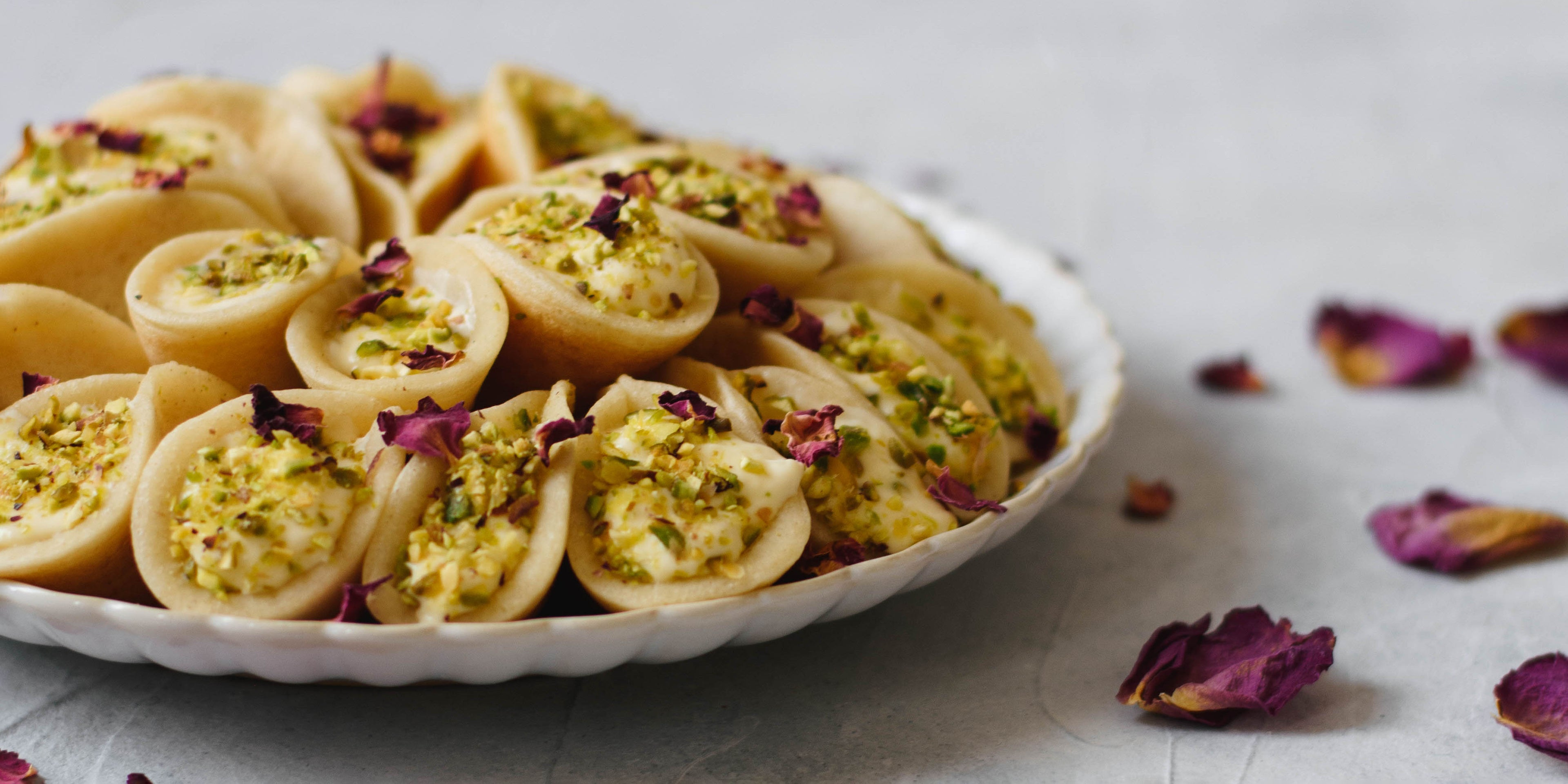 Qatayef on a plate next to petals for decoration