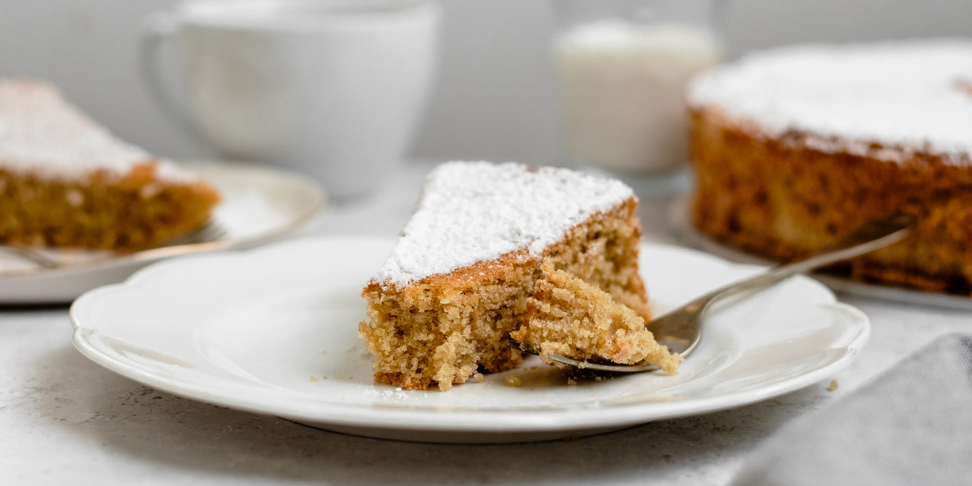 Close up slice of Tarta de Santiago dusted with icing sugar, on a plate with a fork with a bite taken out of it