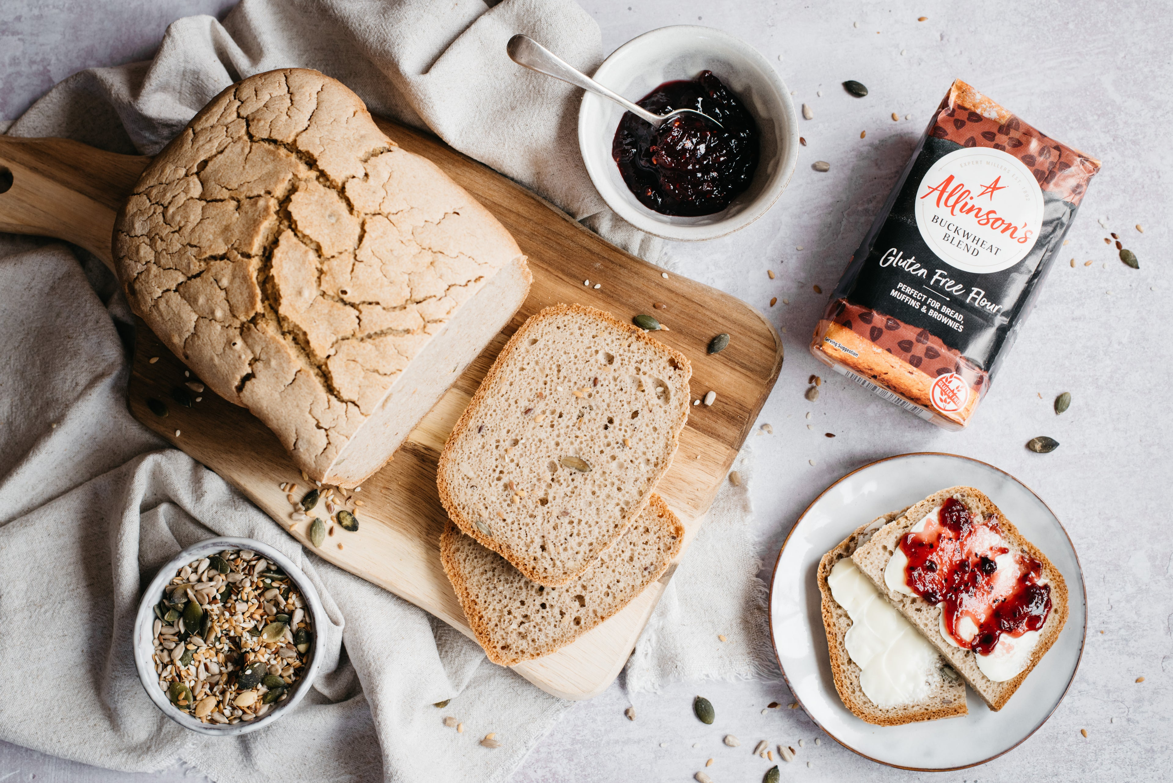 Gluten Free loaf with slices laid infront, flour pack, bowl of seeds and jam