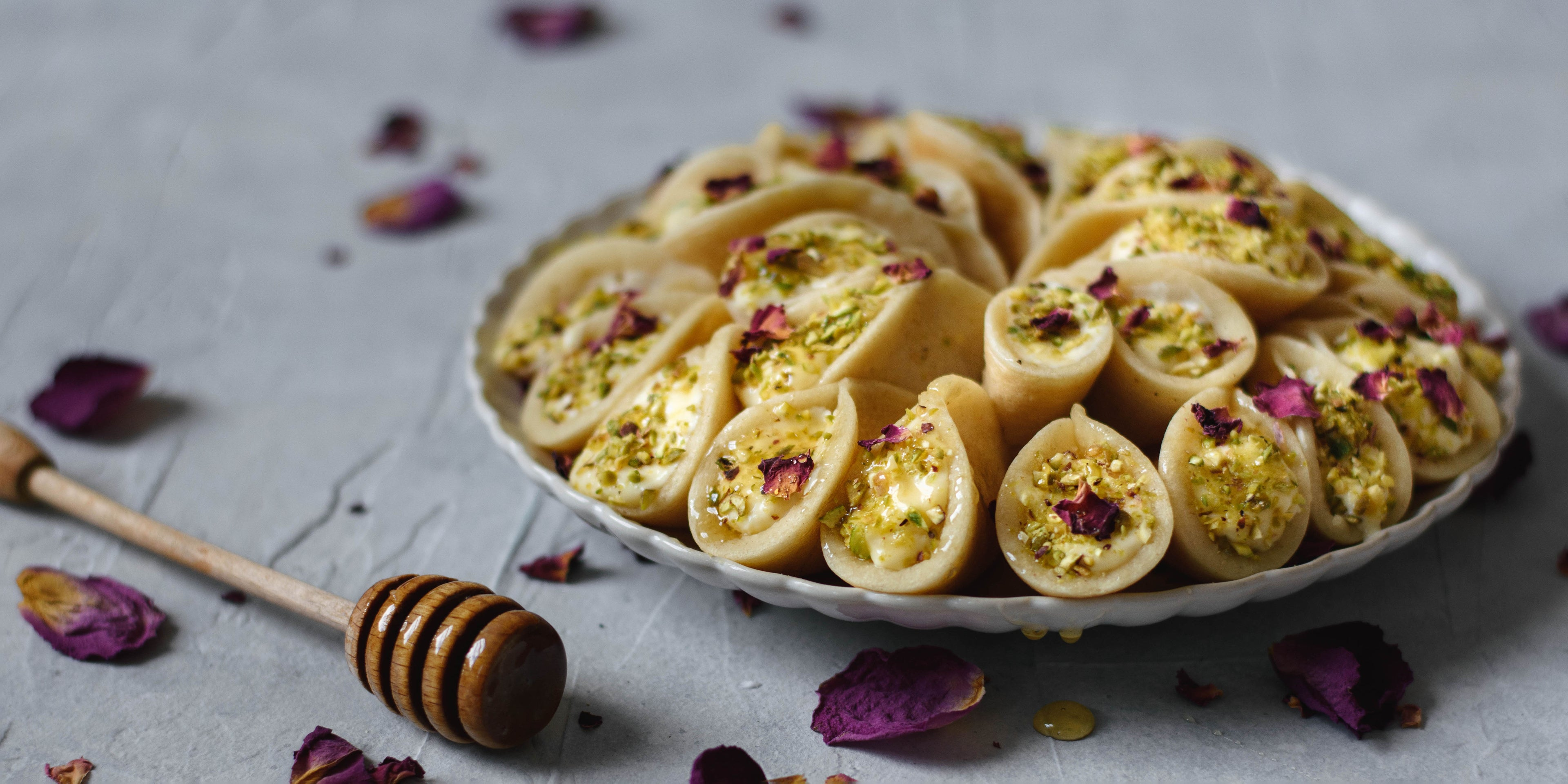 Plate of Qatayef with honey drizzler and petals
