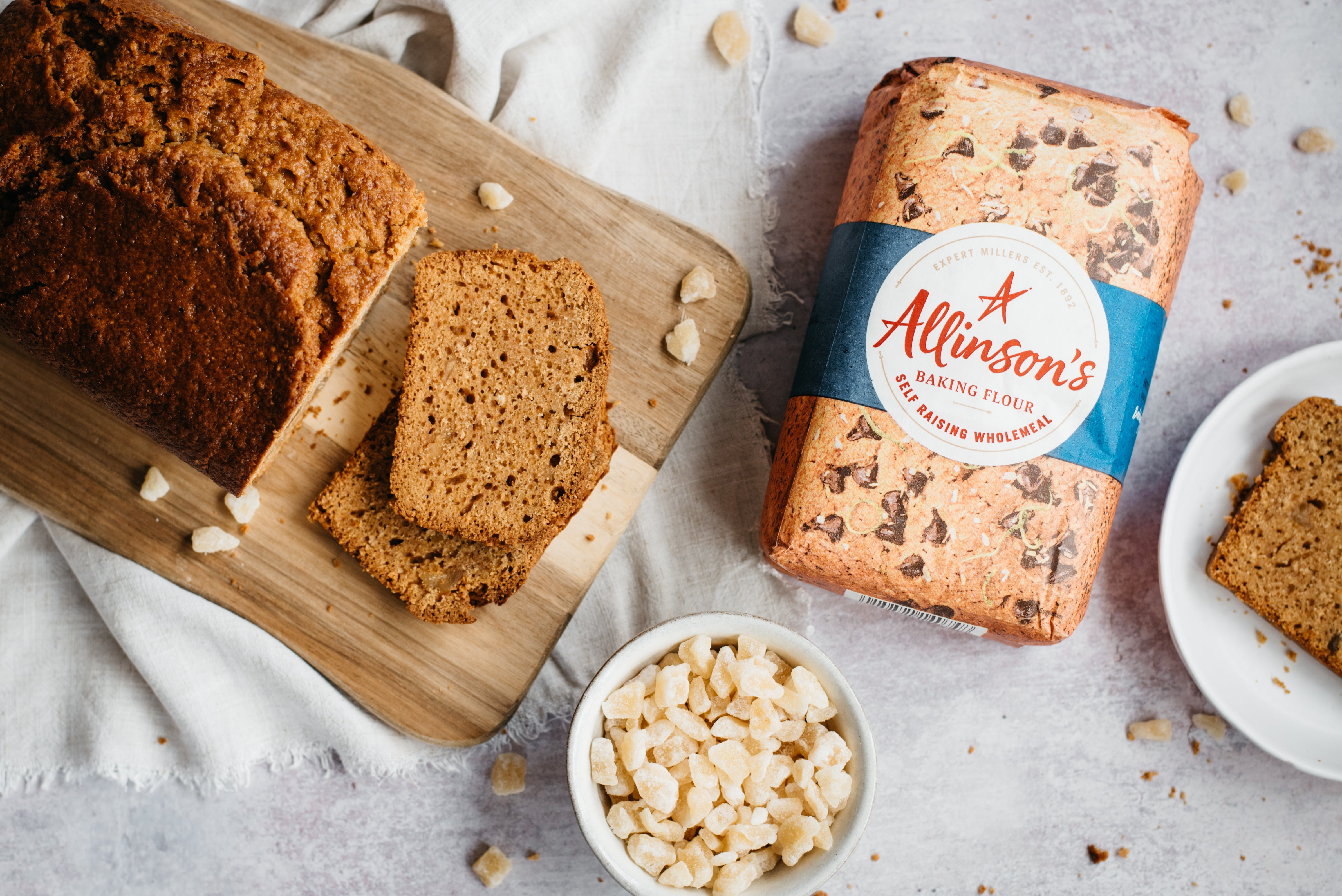 Top view of Gingerbread Loaf on a wooden serving board, next to a bowl of crystallised ginger and a bag of Allinson's self raising flour