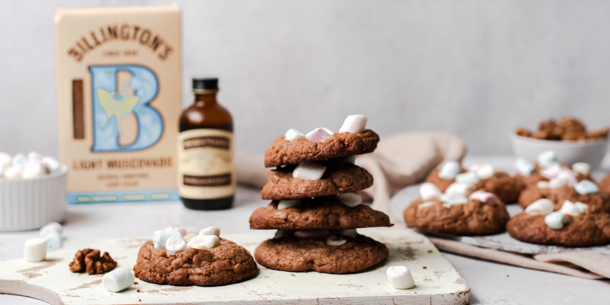 Rocky Road Cookies stacked on top of each other on a serving board, next to a bottle of Neilsen-Massey Vanilla extract, with a box of Billington's Light Muscovado sugar behind