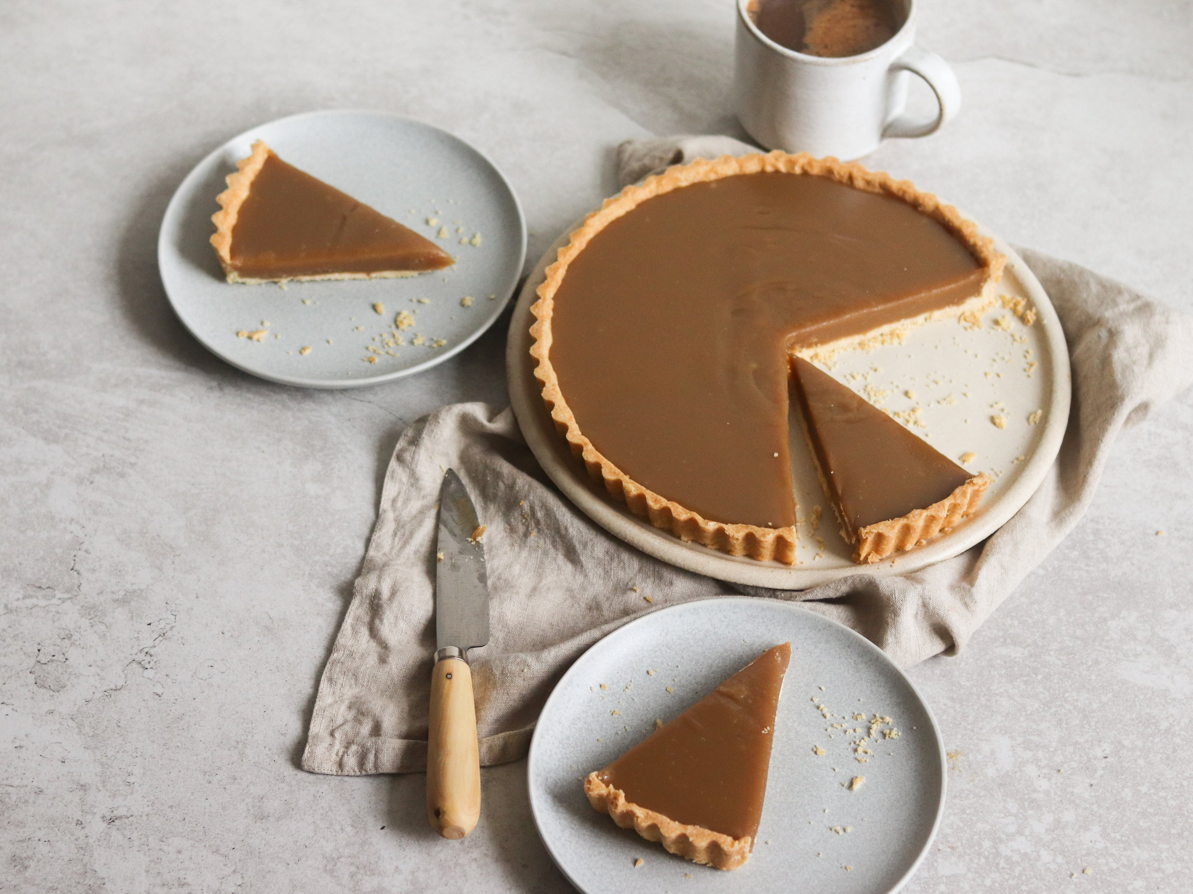 Slices of Butterscotch Tart sliced up onto plates, lay on top of linen