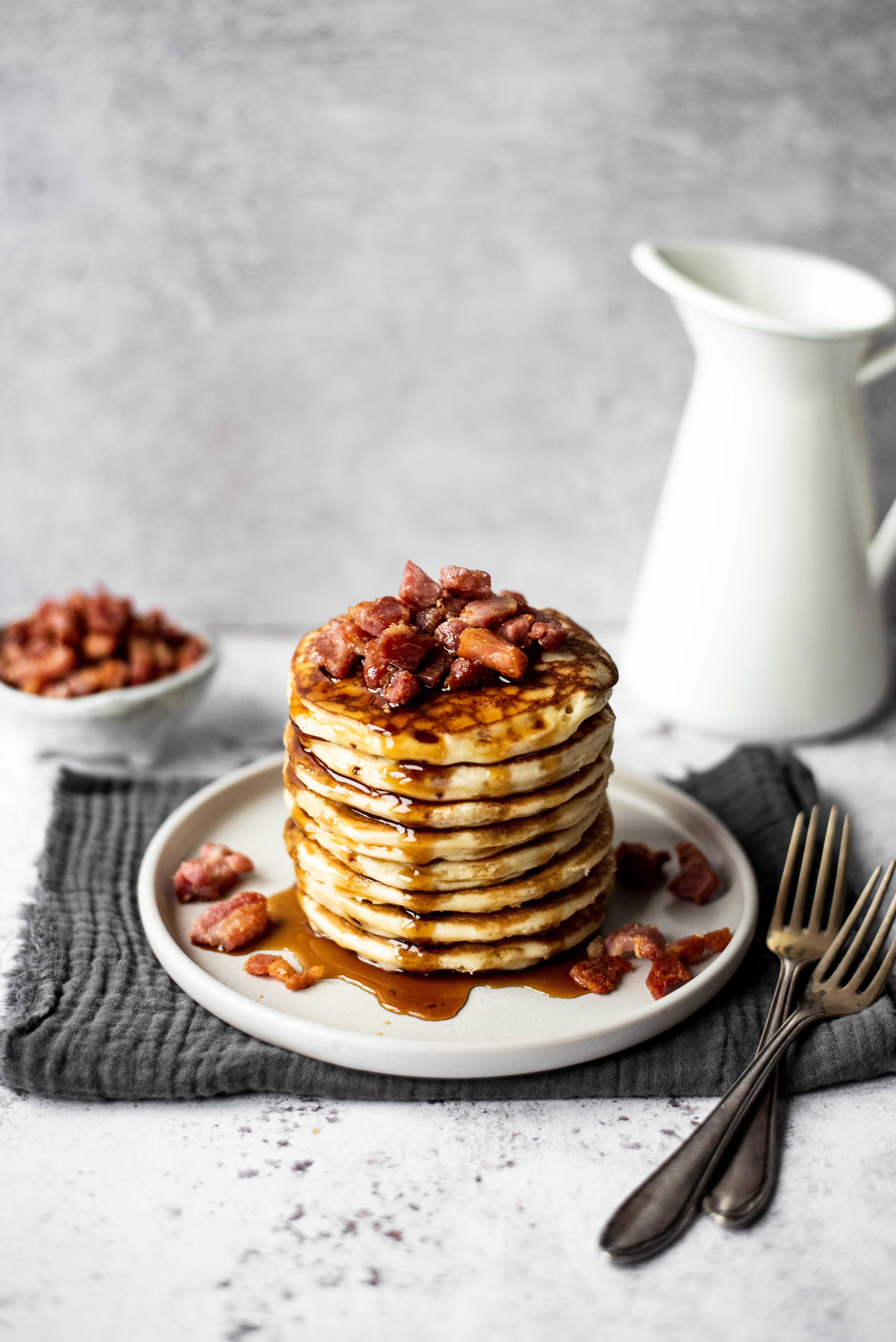 Stack of pancakes topped with bacon and maple syrup