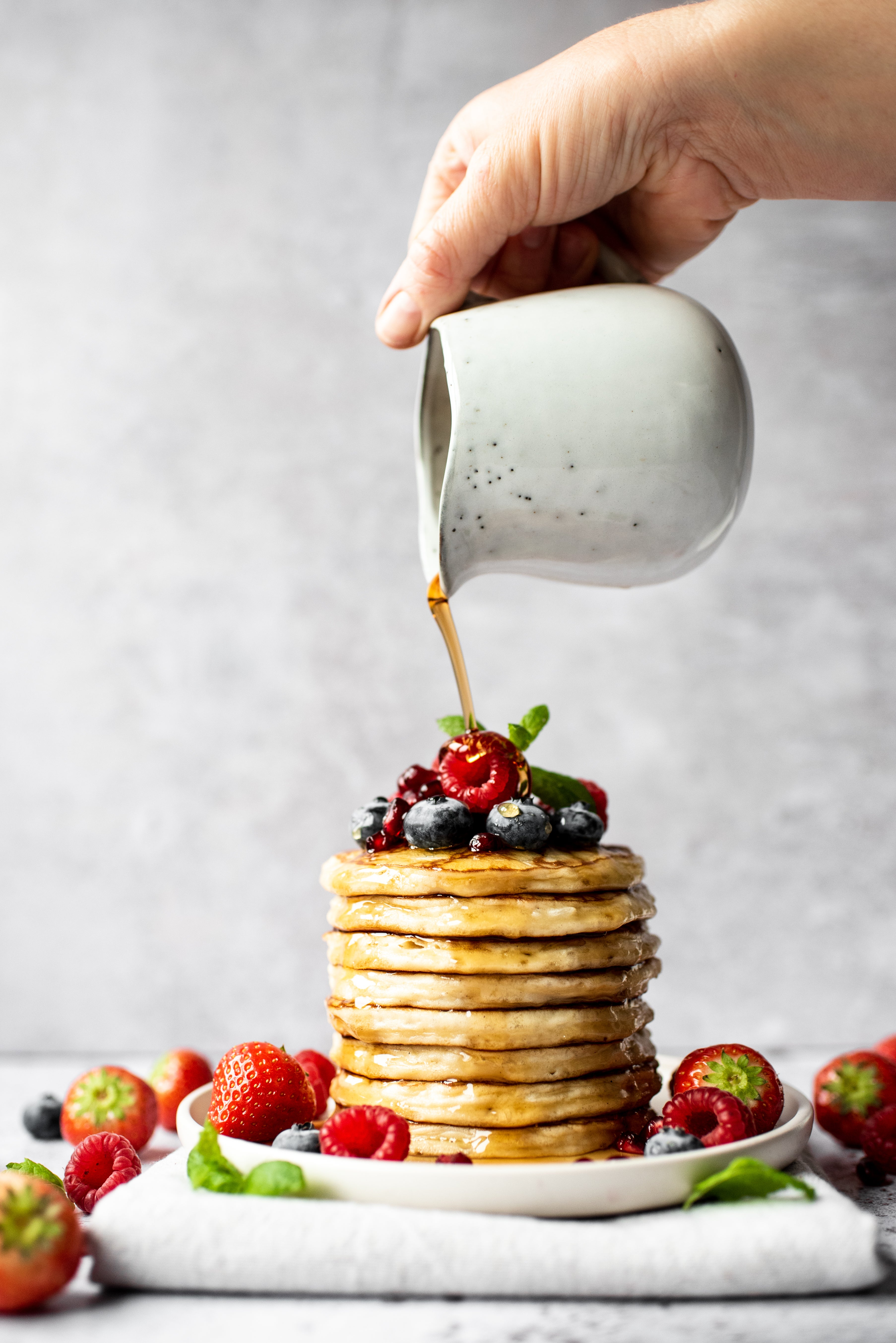 Stack   of pancakes topped with fresh berries and a hand pouring maple syrup from a jug