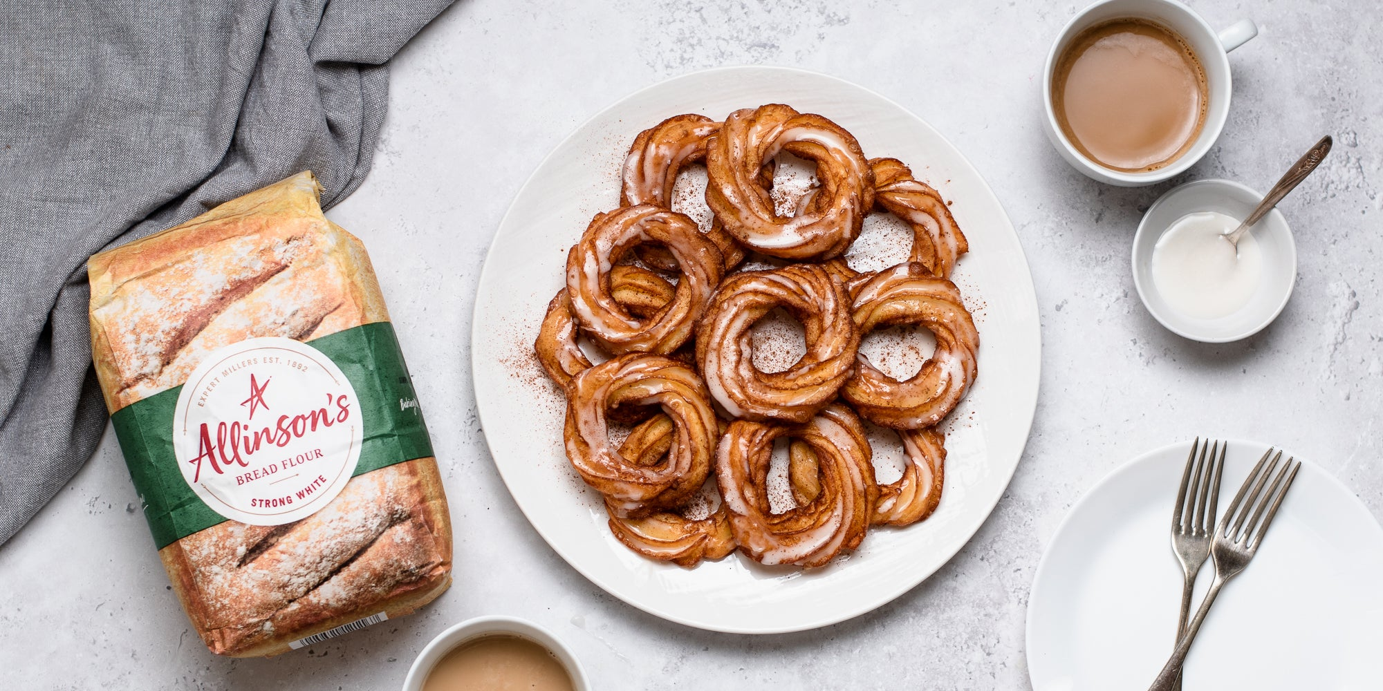 Apple Cider Crullers on a plate, next to a bag of Allinson's Strong White Flour, topped with icing.