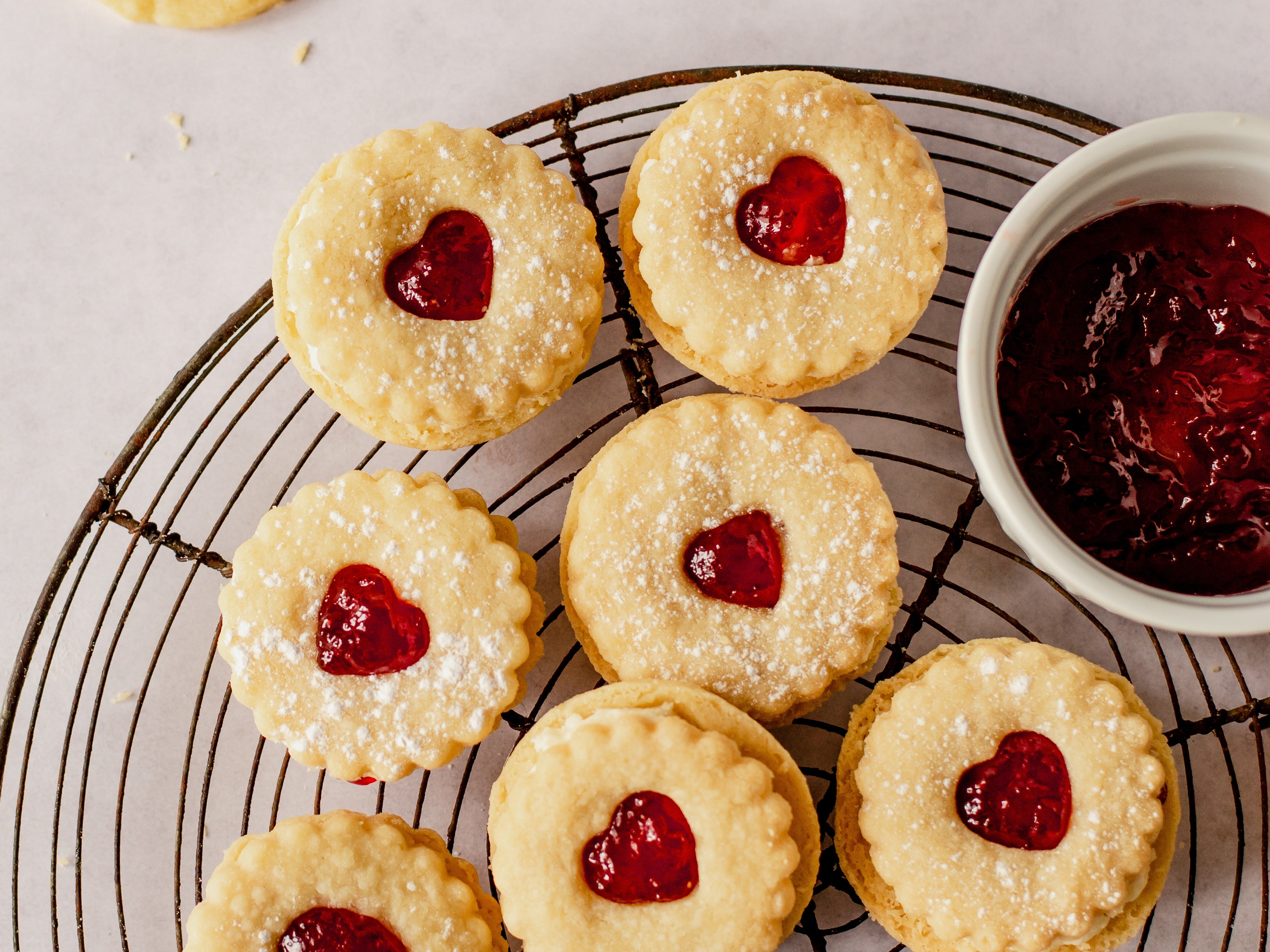 Close up of jammy dodgers on a wire cooling rack with bowl of jam