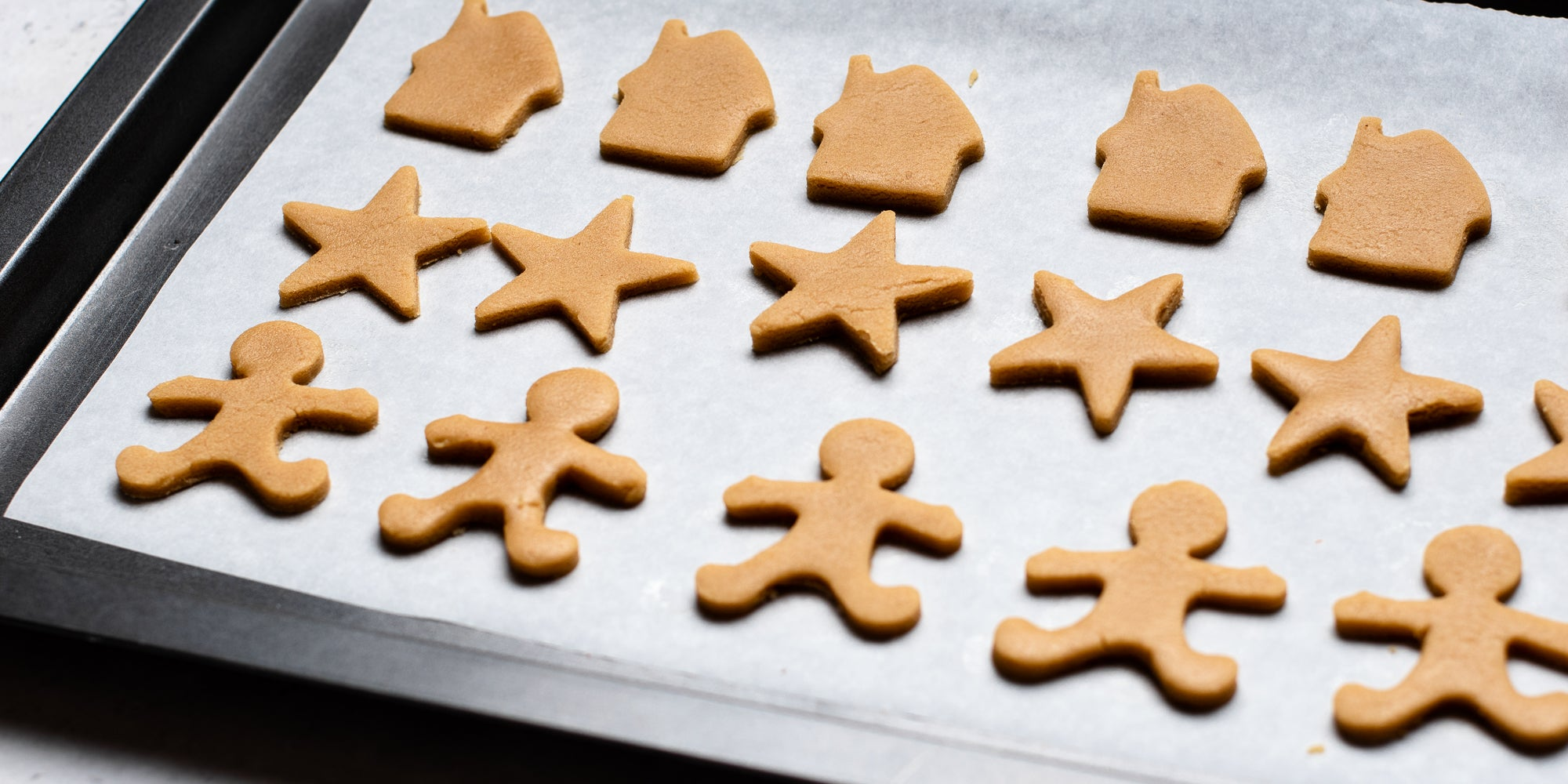 Shapes cut from Gingerbread Dough including, gingerbread men, stars and gingerbread houses lay on baking paper on a baking tray