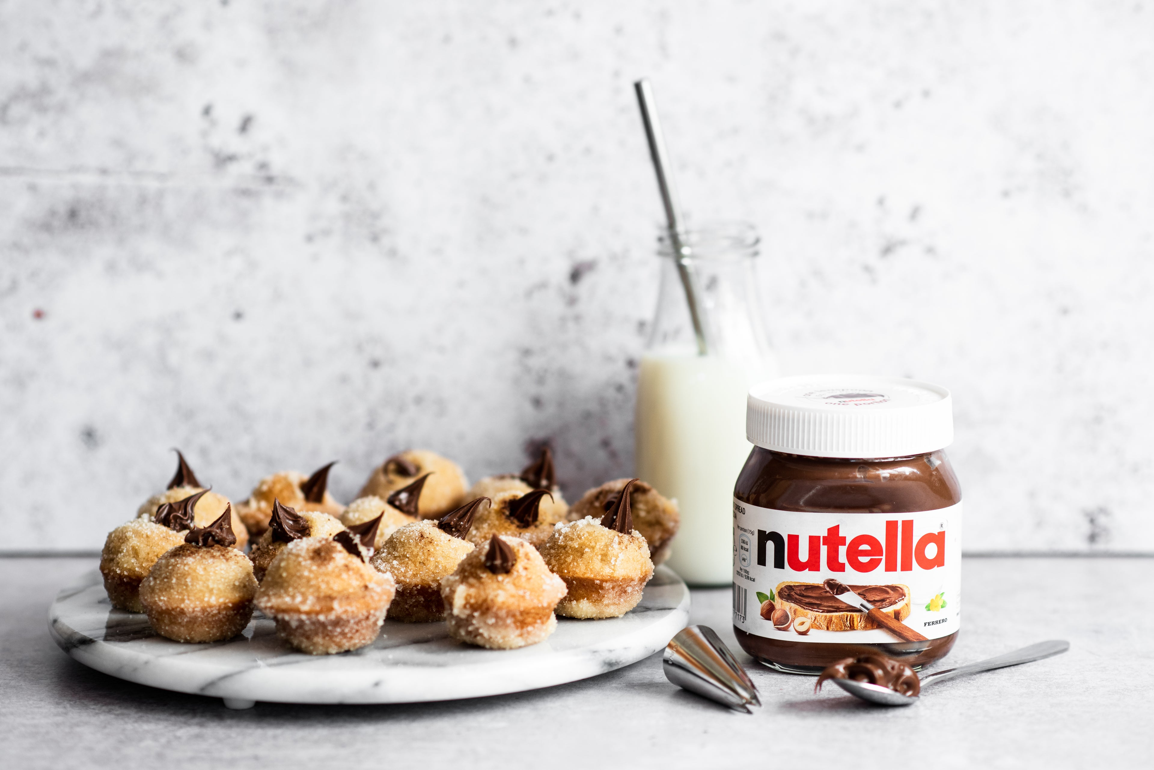 Plate of Nutella filled doughnuts next to a jar of Nutella