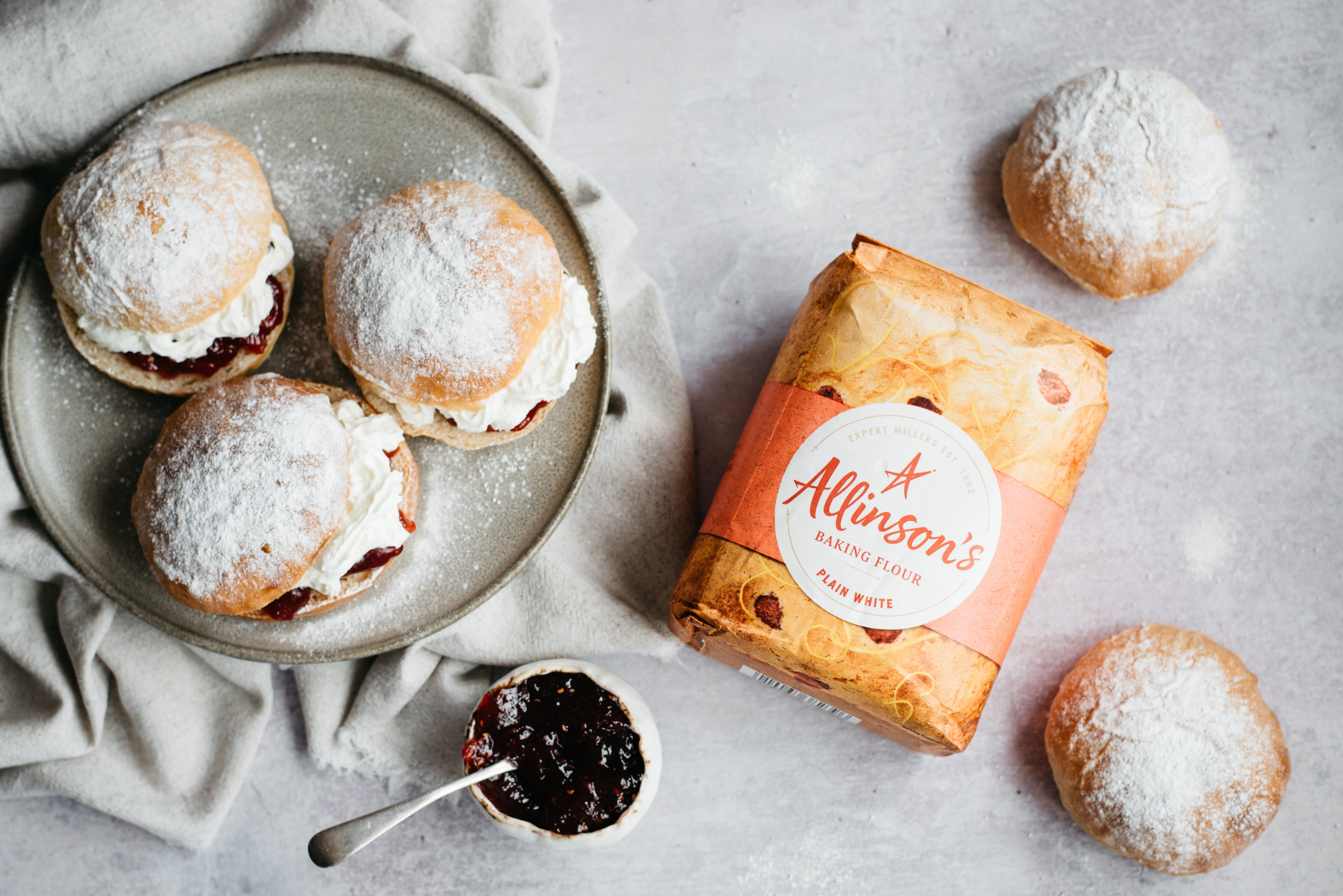 Flat lay of Devonshire Splits next to a bag of Allinson's plain flour and a bowl of jam.