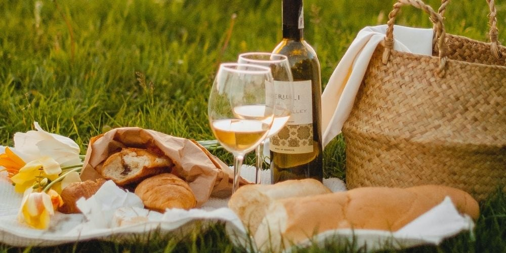 Blanket on grass, with flowers, bread, wine glass and bottle