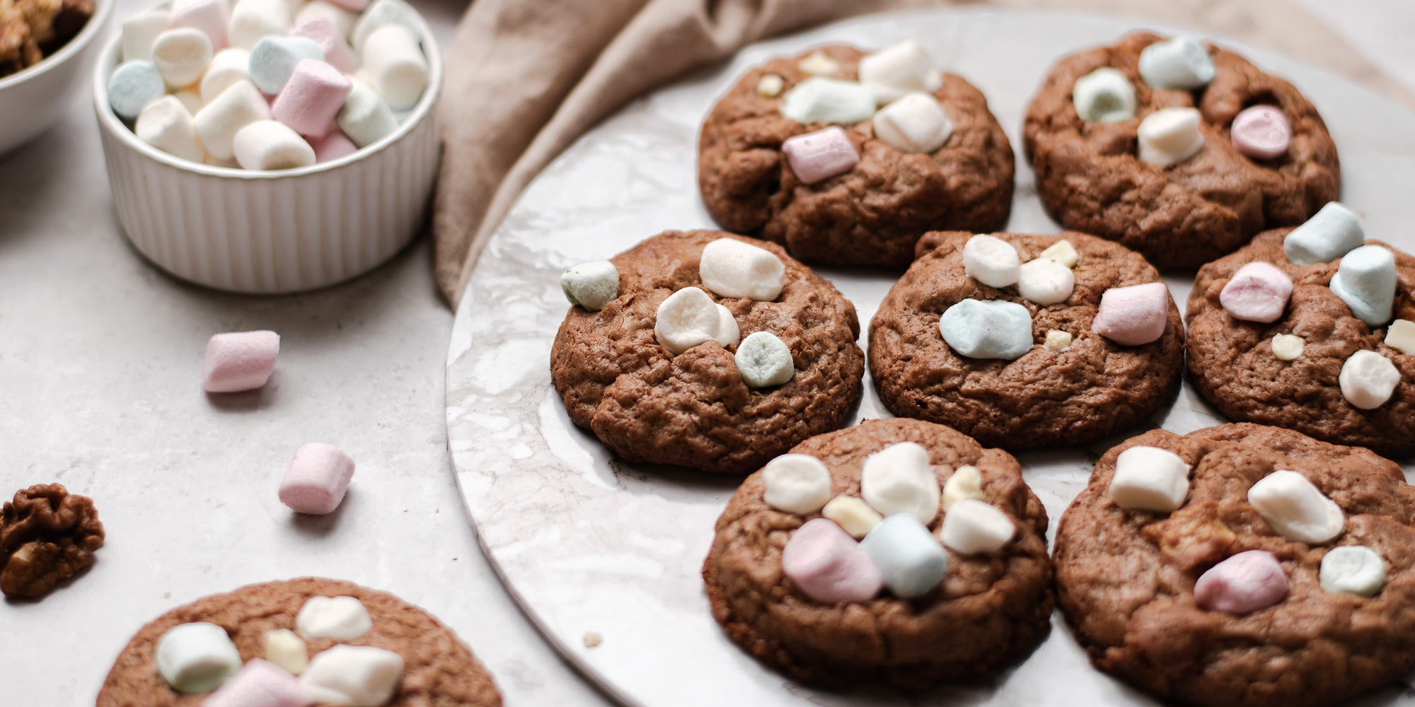 A batch of Rocky Road Cookies topped with marshmallows next to a ramekin of mini marshmallows