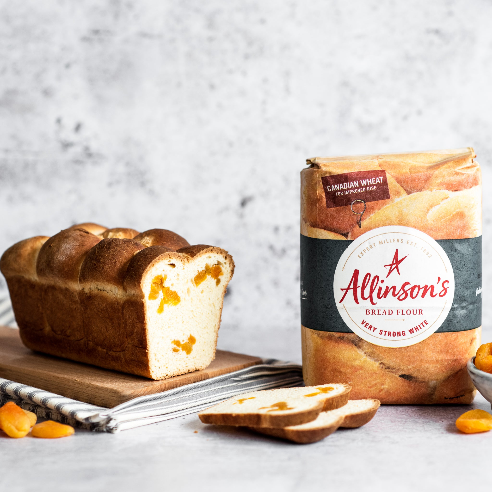 Brioche loaf on bread board with two slices cut in front and Allinson's flour pack