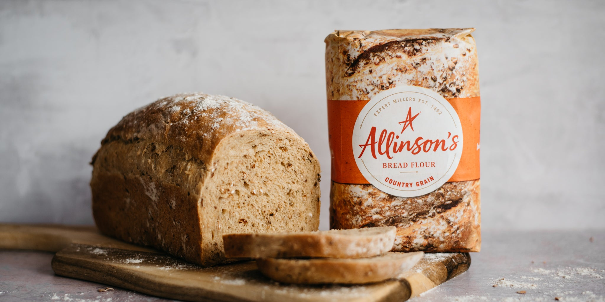 Farmhouse Country Grain Loaf sliced on a serving board, next to a bag of Allinson's Country Grain flour