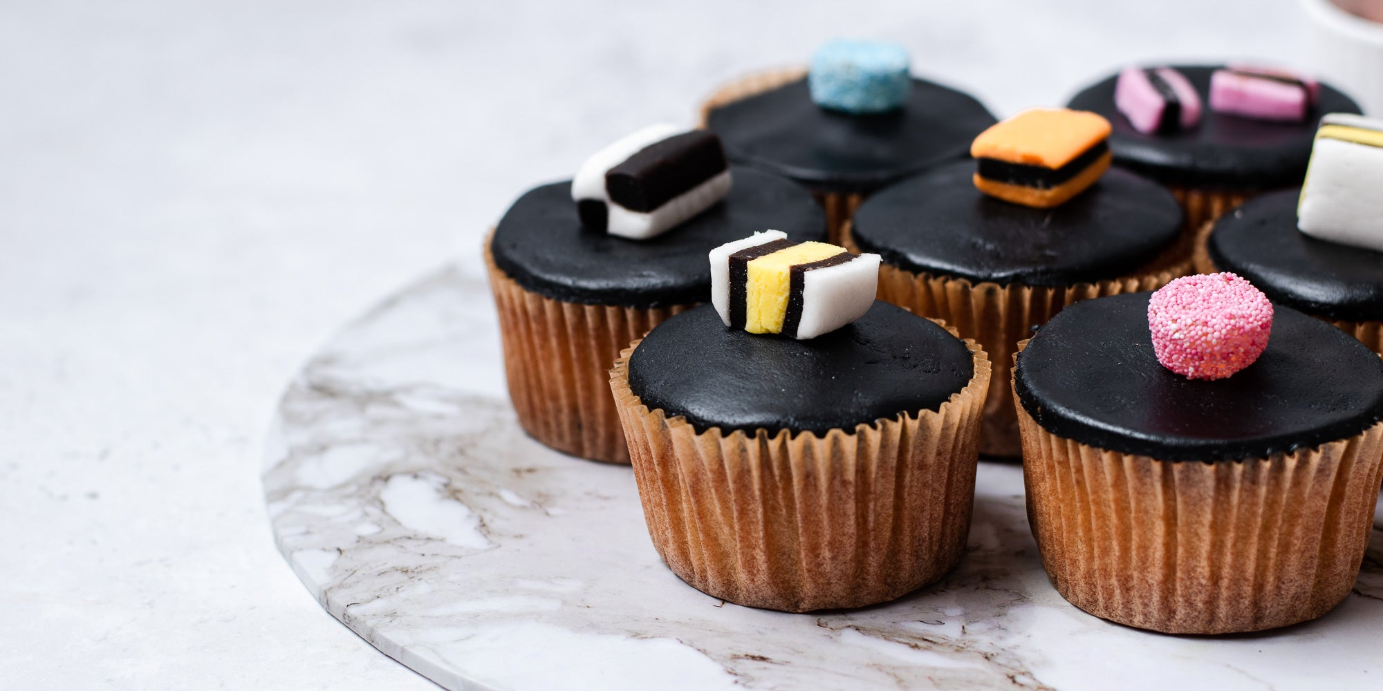Cupcakes in brown cases, black fondant, topped with liquorice allsorts