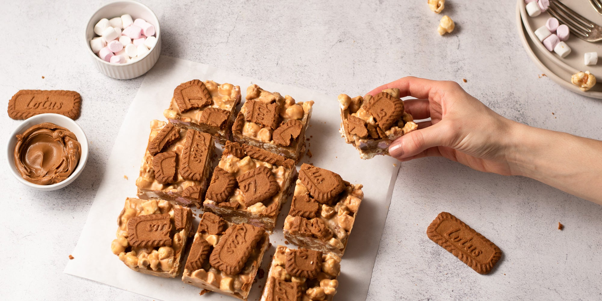 Biscoff rocky road sliced into 9 pieces with a hand taking one slice