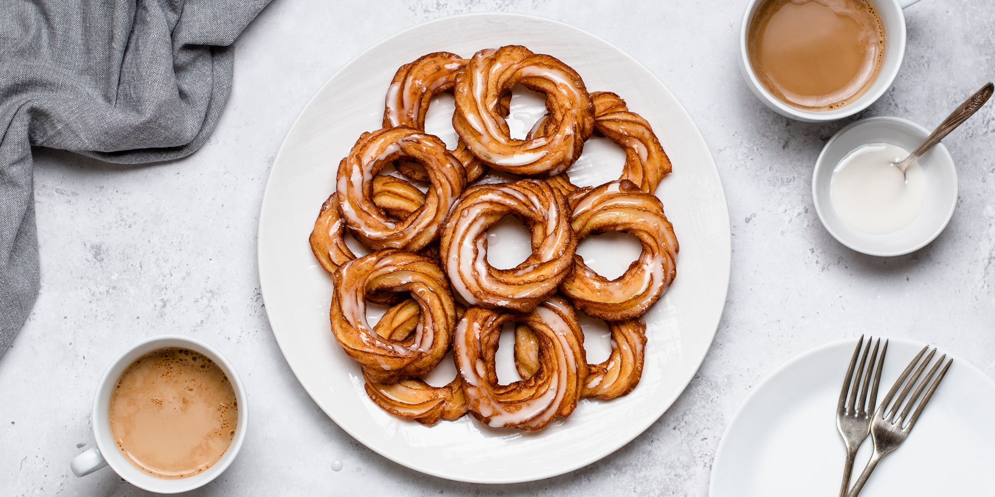 Top view of Apple Cider Crullers on a plate. Next to cups of coffee, and a bowl of icing ready to decorate
