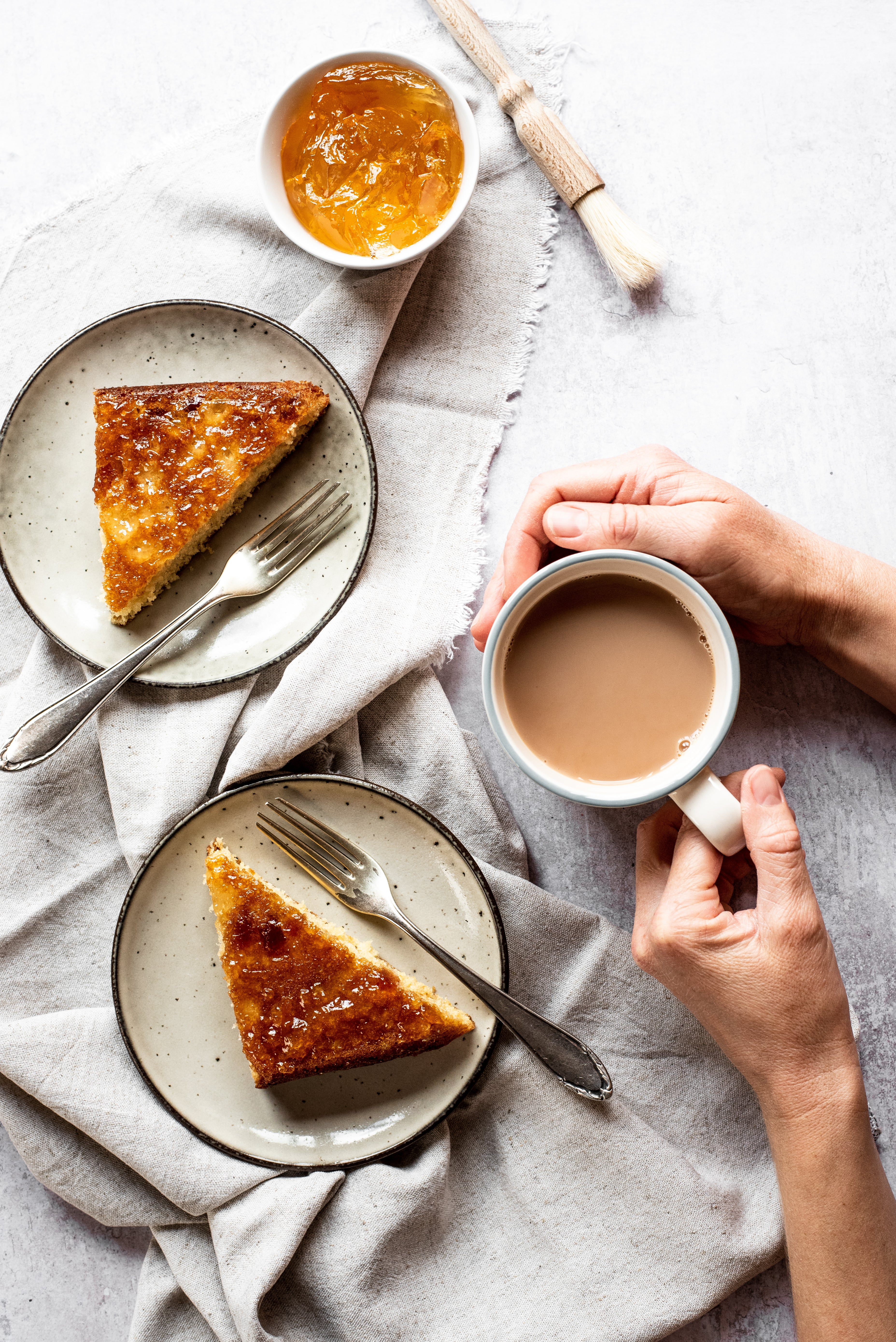 Top view of Marmalade Traybake, served on plates with forks. Plates are lay on top of linen cloths, next to hands holding a mug of tea