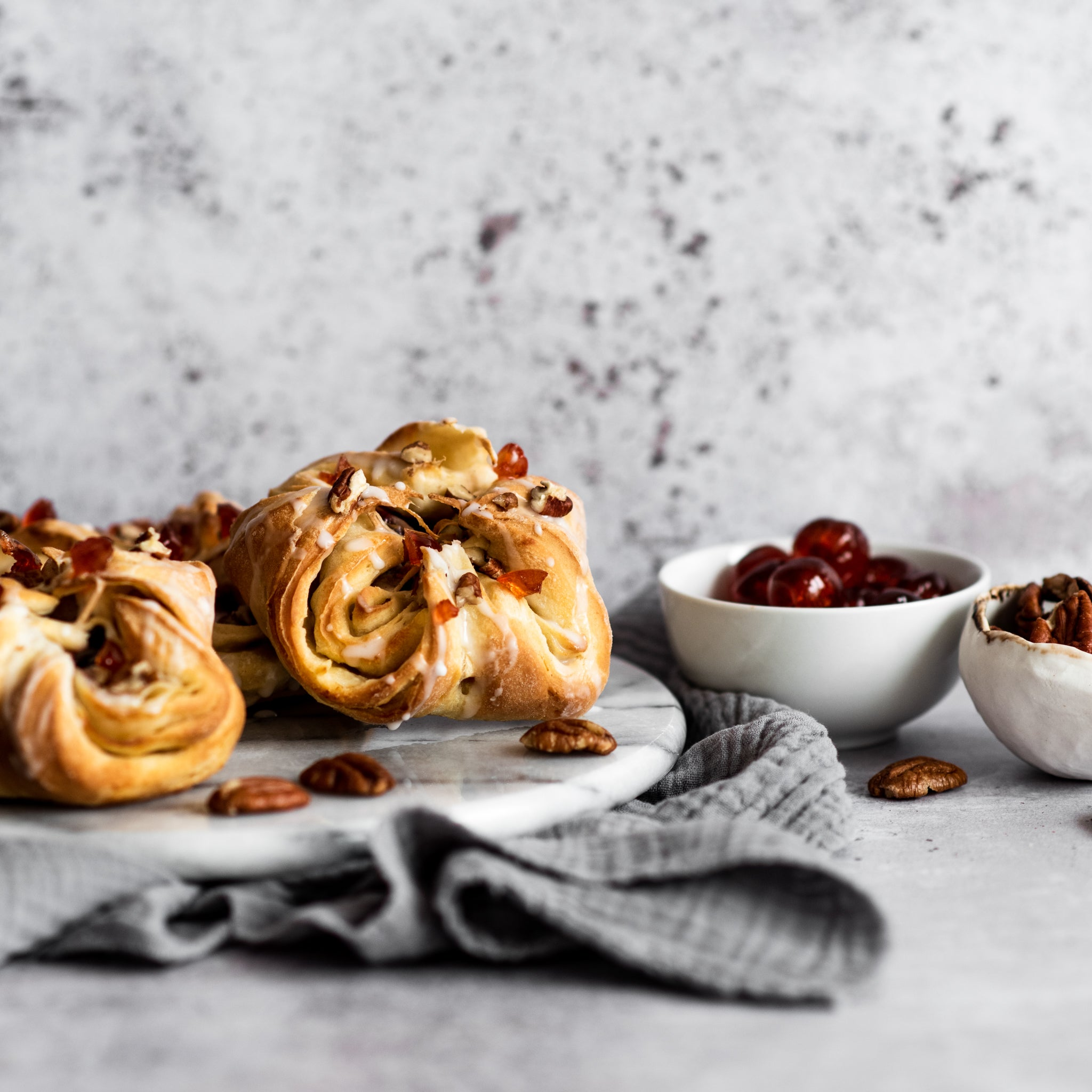 Close up of two danish pastries and bowl of pecans and cherries