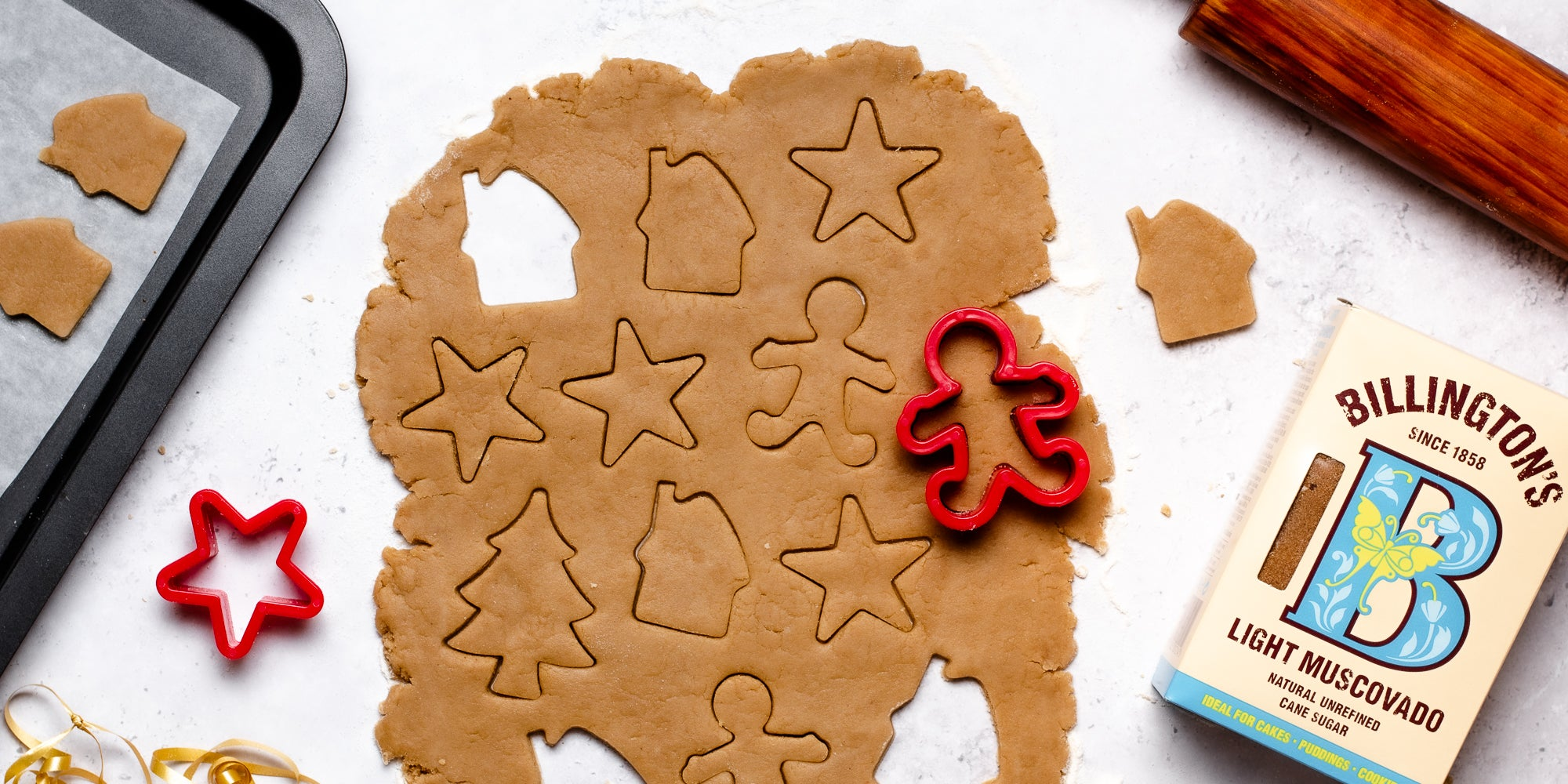 Top down view of a gingerbread man cookie cutter cutting out vegan gingerbread dough