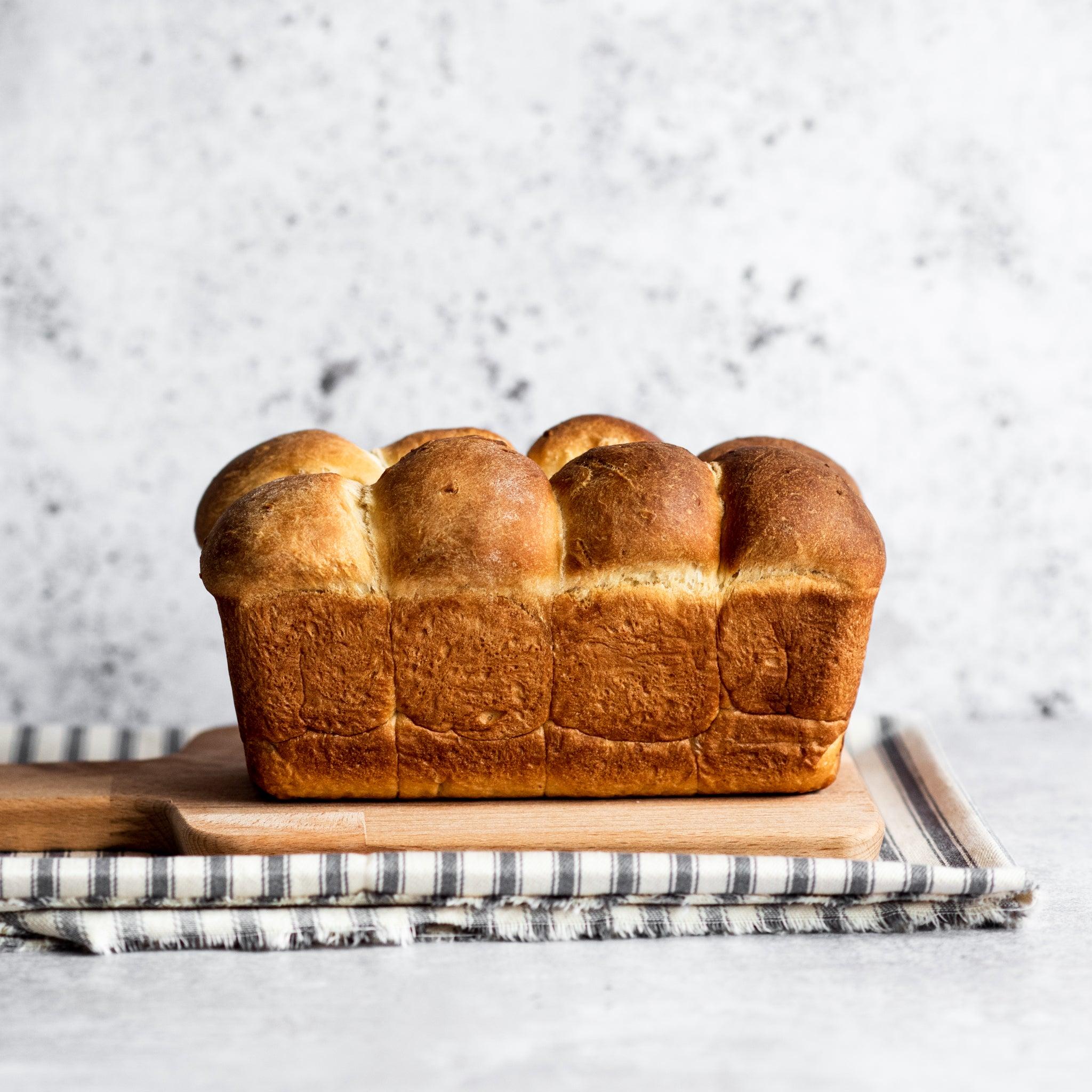 Side on shot of brioche loaf, uncut on bread board